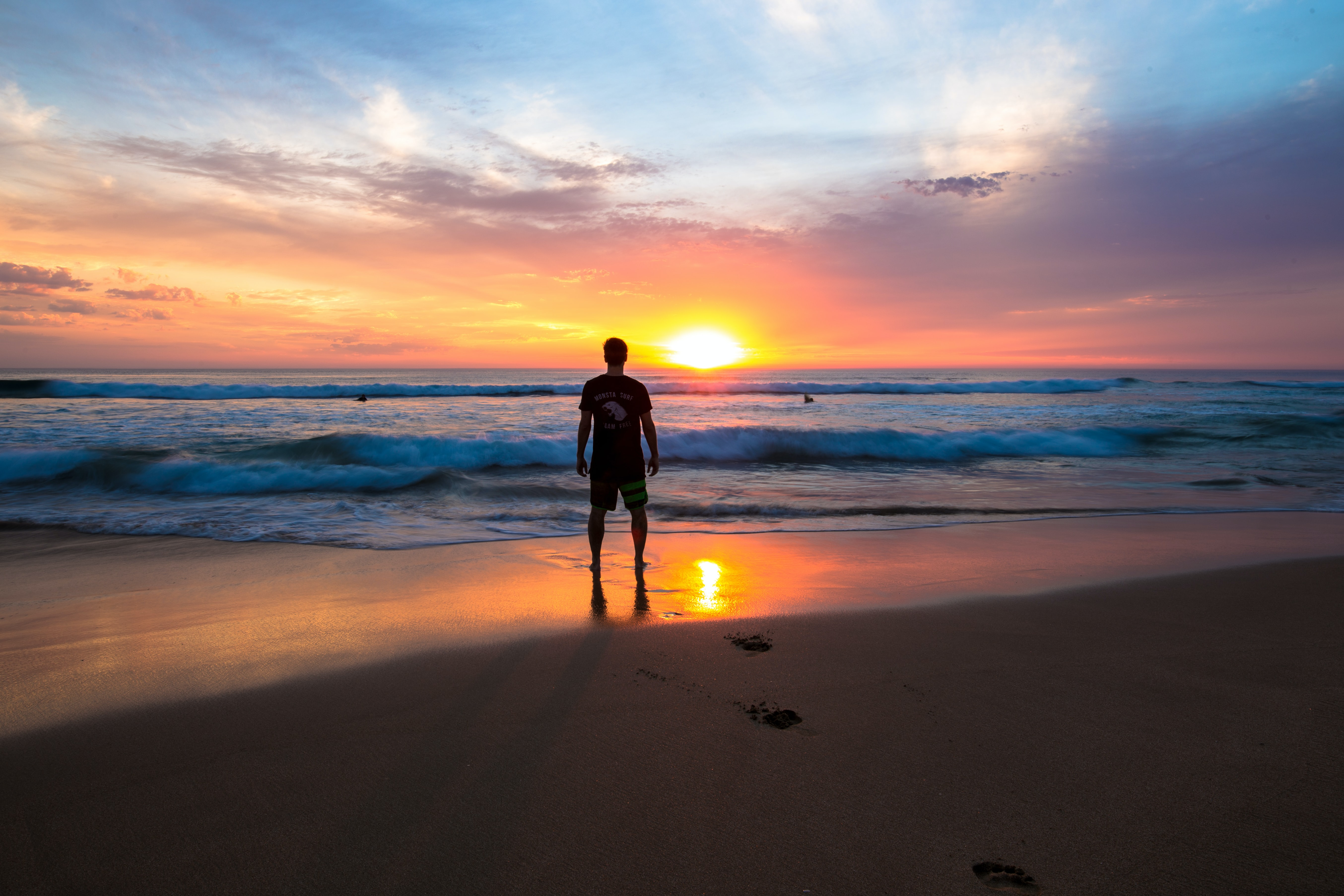 Man standing on the sands of Gunnamatta Ocean Beach watching the sunset and the crashing waves