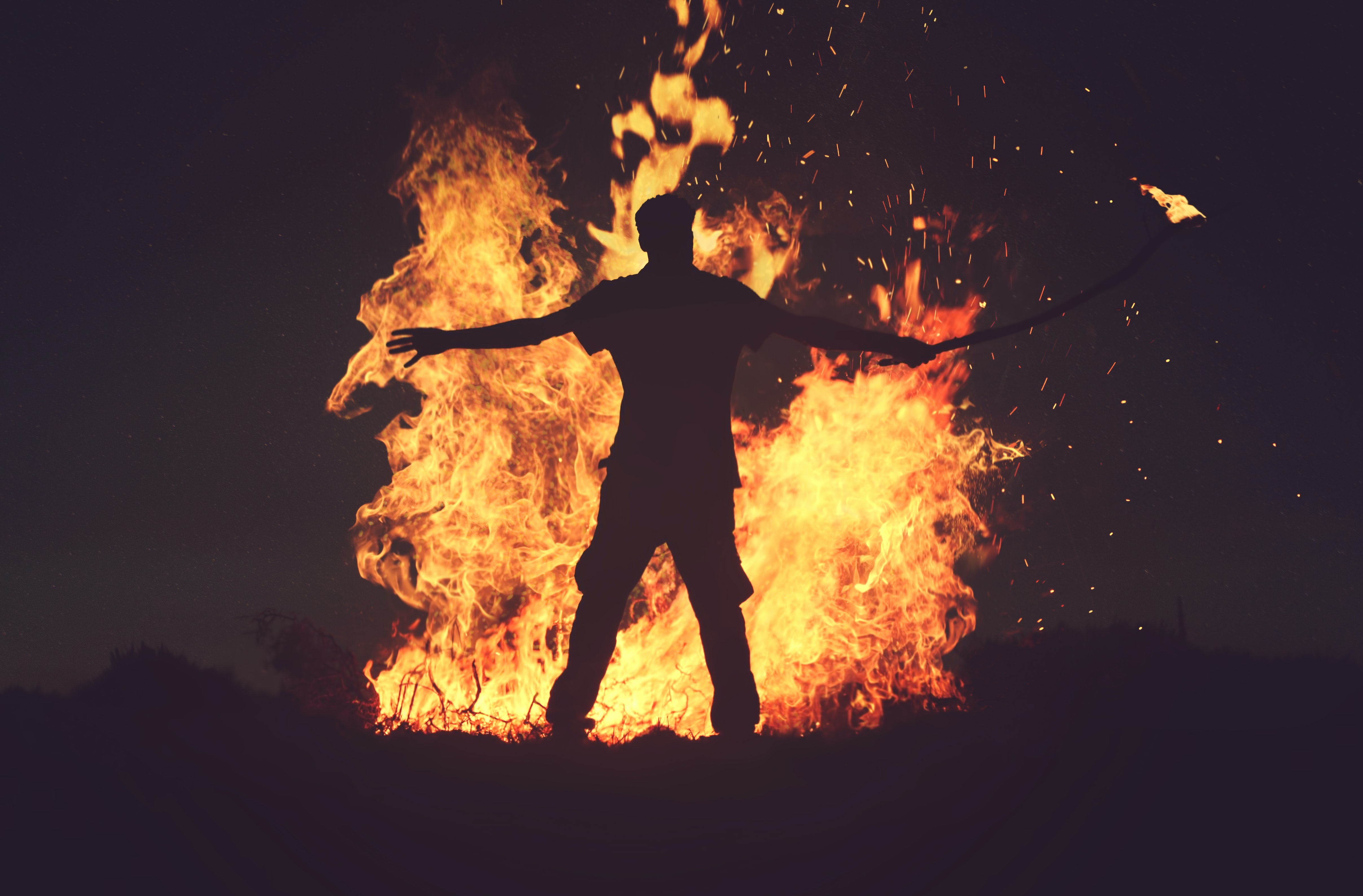 A silhouette of a man holding a burning torch next to a huge bonfire