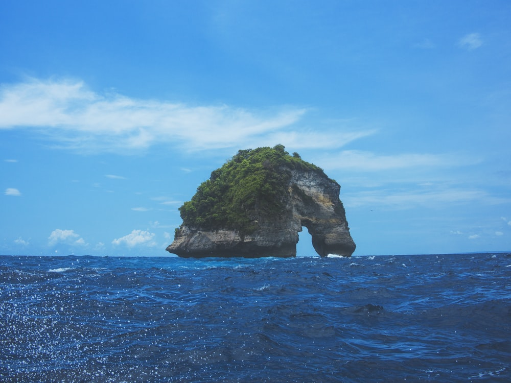 arched rock island under blue and white cloudy sky