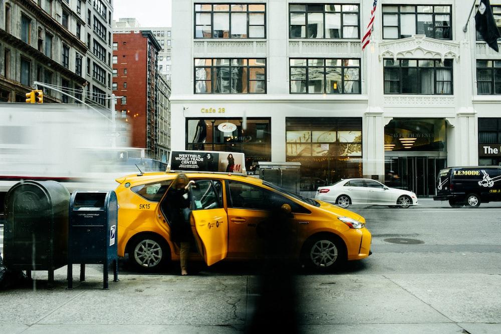 woman going inside yellow car