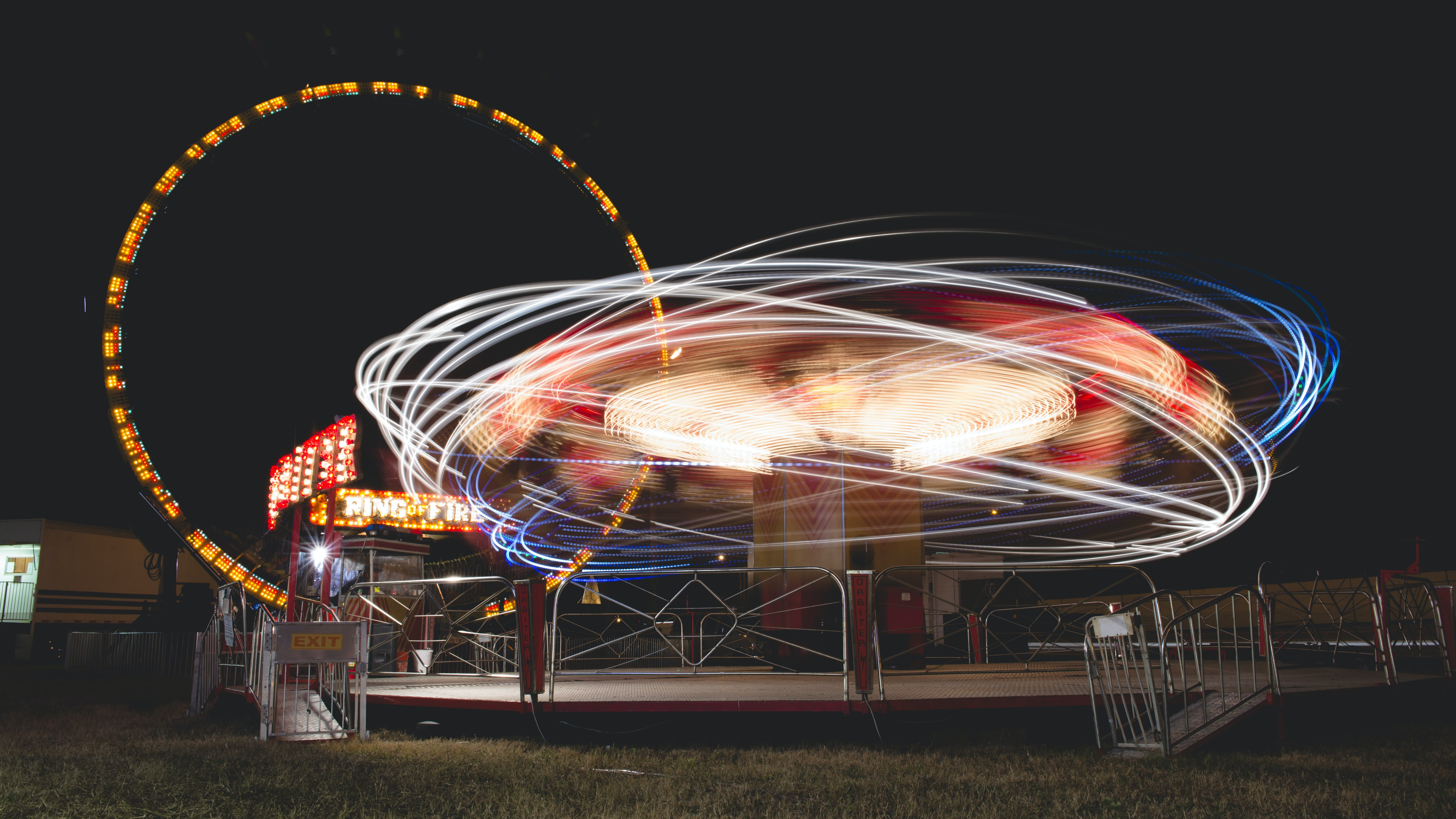 An eccentric, lively image of illuminated carnival rides creating neon light trail patterns in various colors