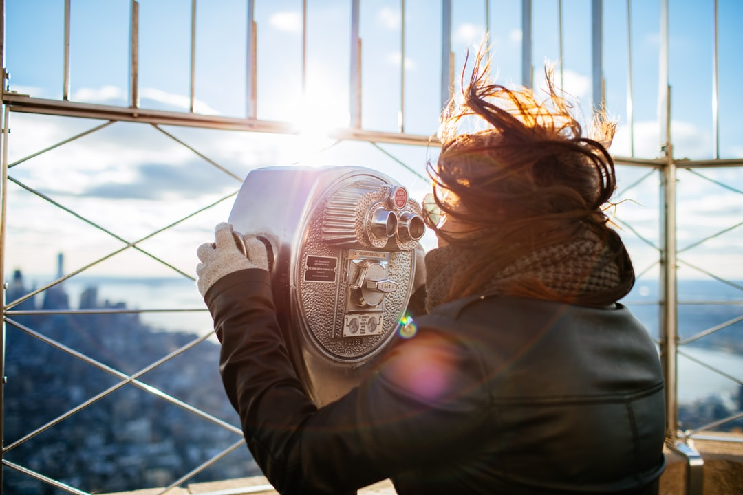 Tourist looking through a viewfinder on a windy day in New York City