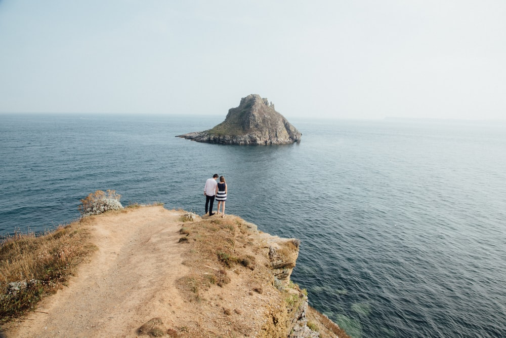 aerial photography of man and woman near cliff