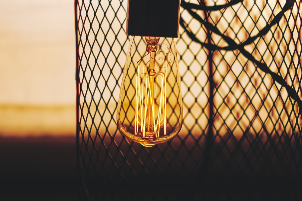 silhouette photo of light bulb near chain-link fence