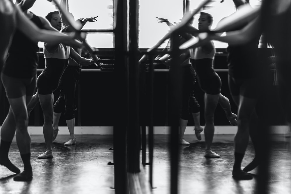 grayscale photo of womens exercising in front of mirror