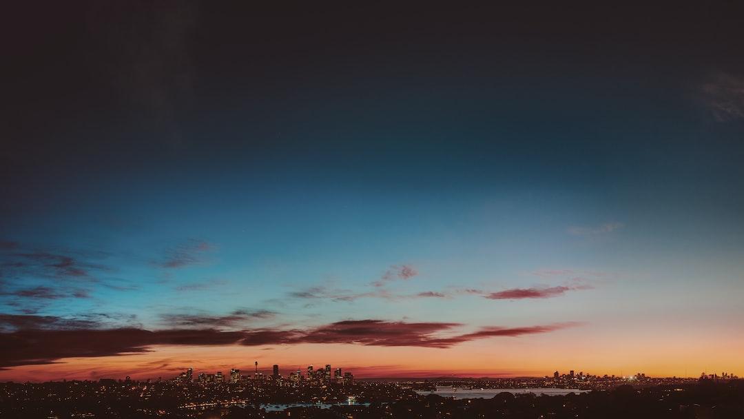 skyline d'una ciutat. és al vespre i el cel es de colors des de blau fosc a la part superior fins a groc a la part més inferior, tocant a uns edificis que es veuen al fons