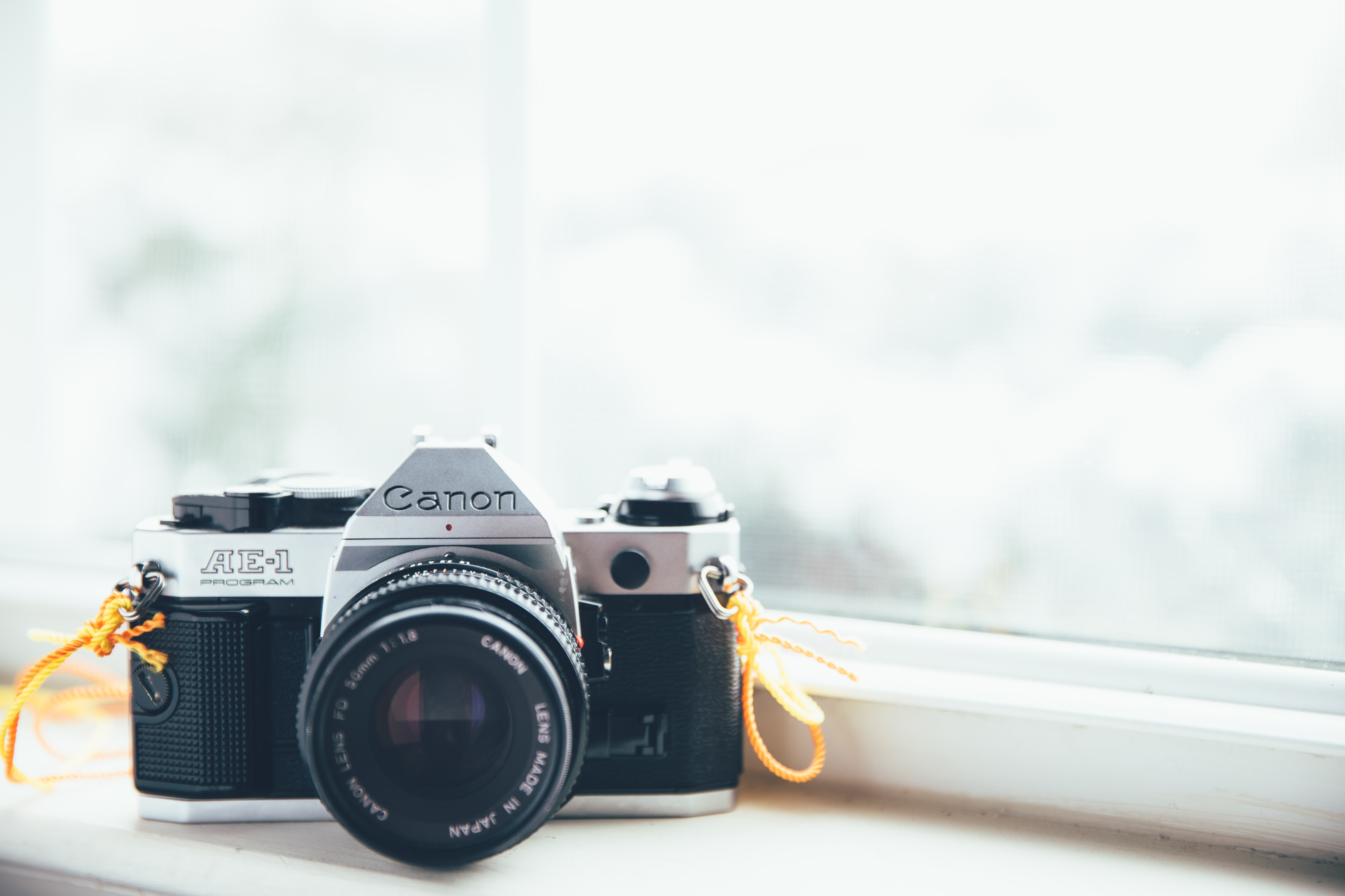 Macro shot of vintage canon camera on window sill with window in background and light