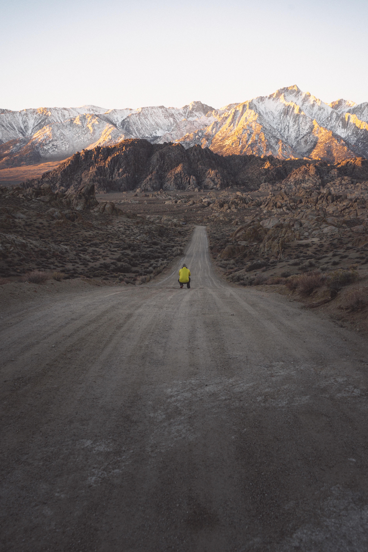 man sitting on road between rock mountains at daytime