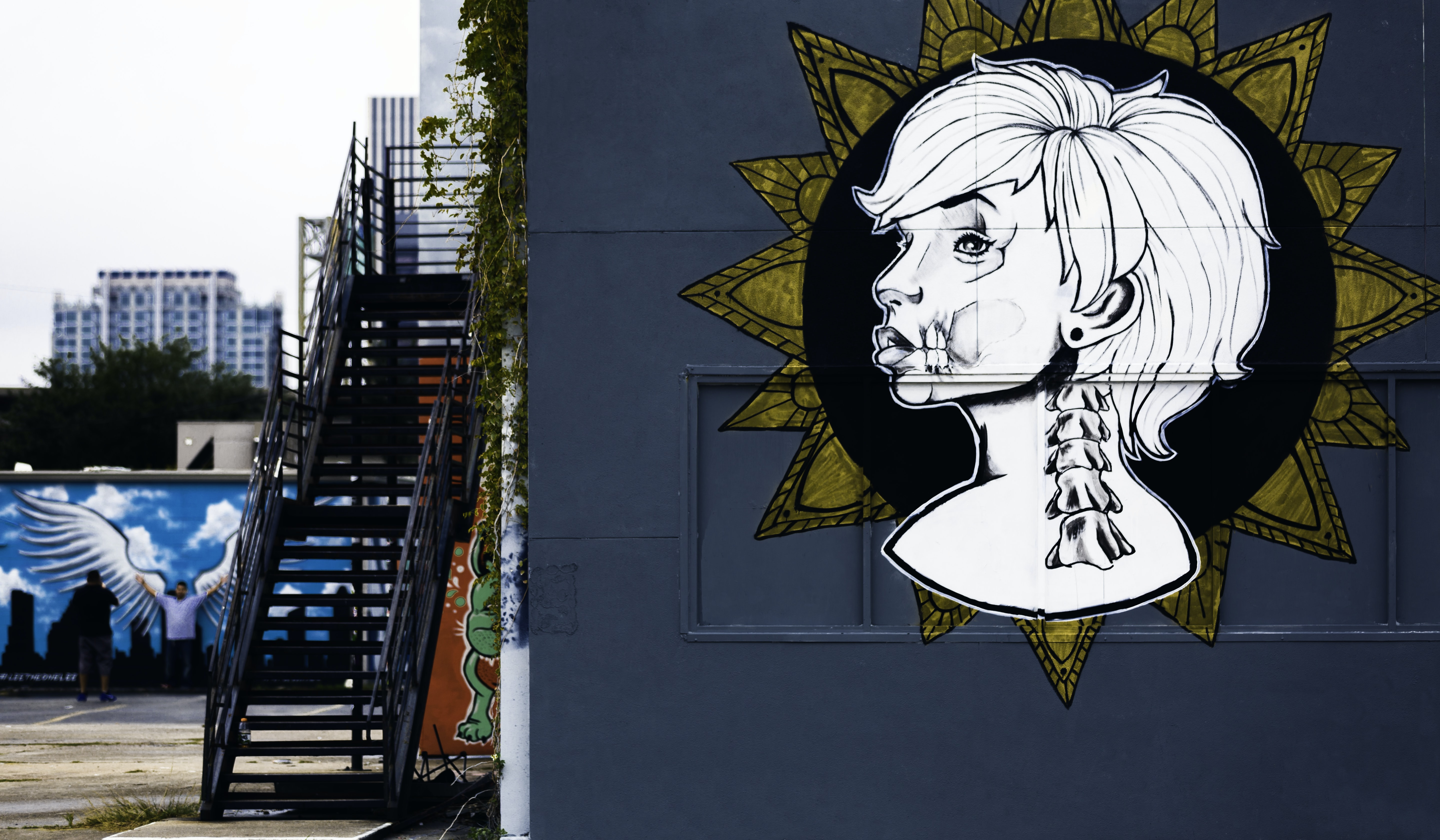 Urban stairwell and white graffiti of woman's face and head on urban building in Houston