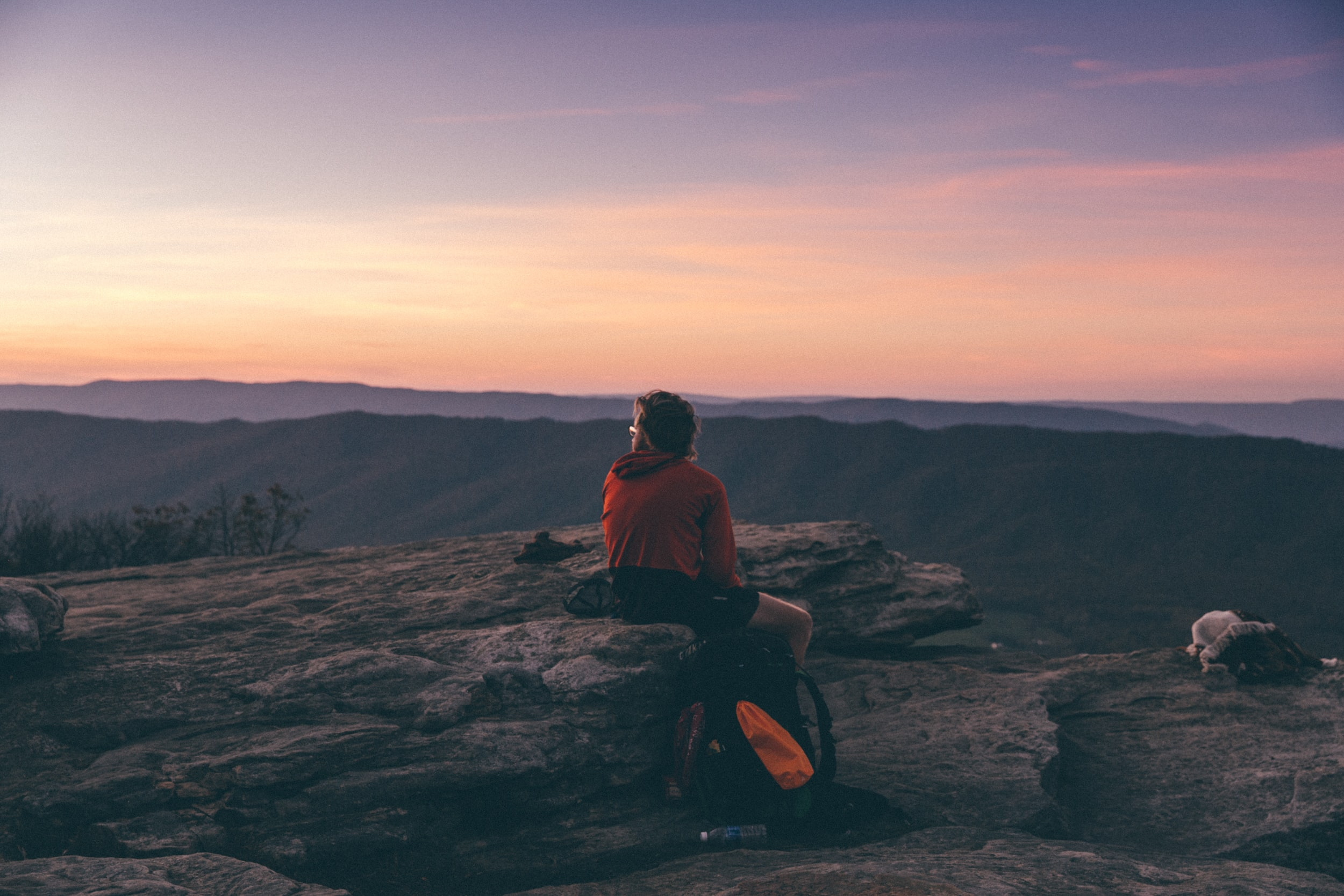 person sitting on boulder overlooking mountain during golden hour