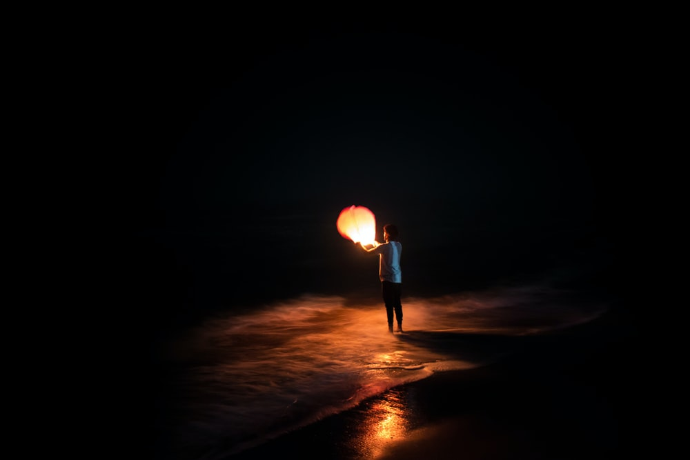person standing on shore holding brown paper lantern
