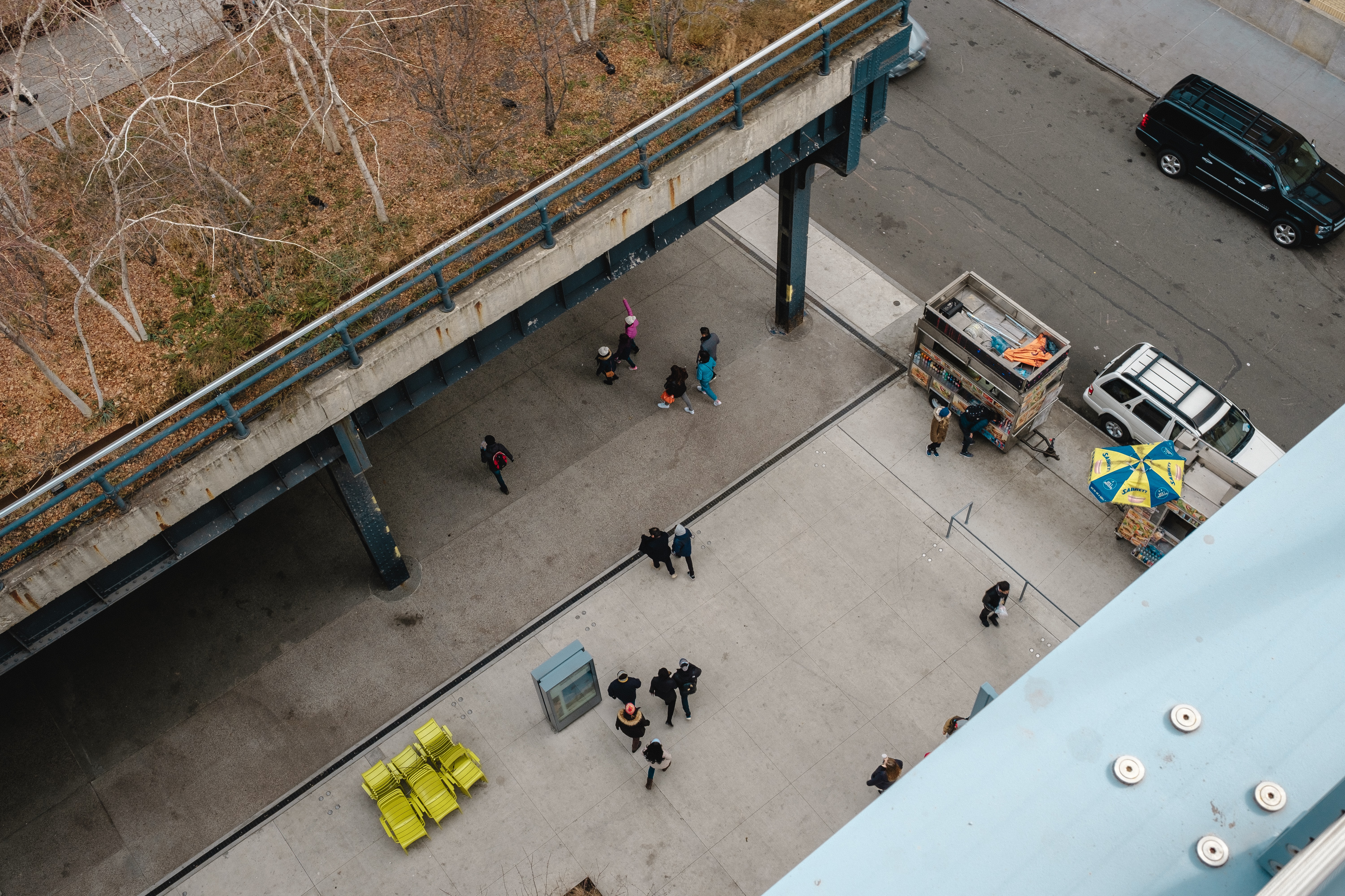 Looking down from the rooftop of Whitney Museum of American Art at people crossing the square