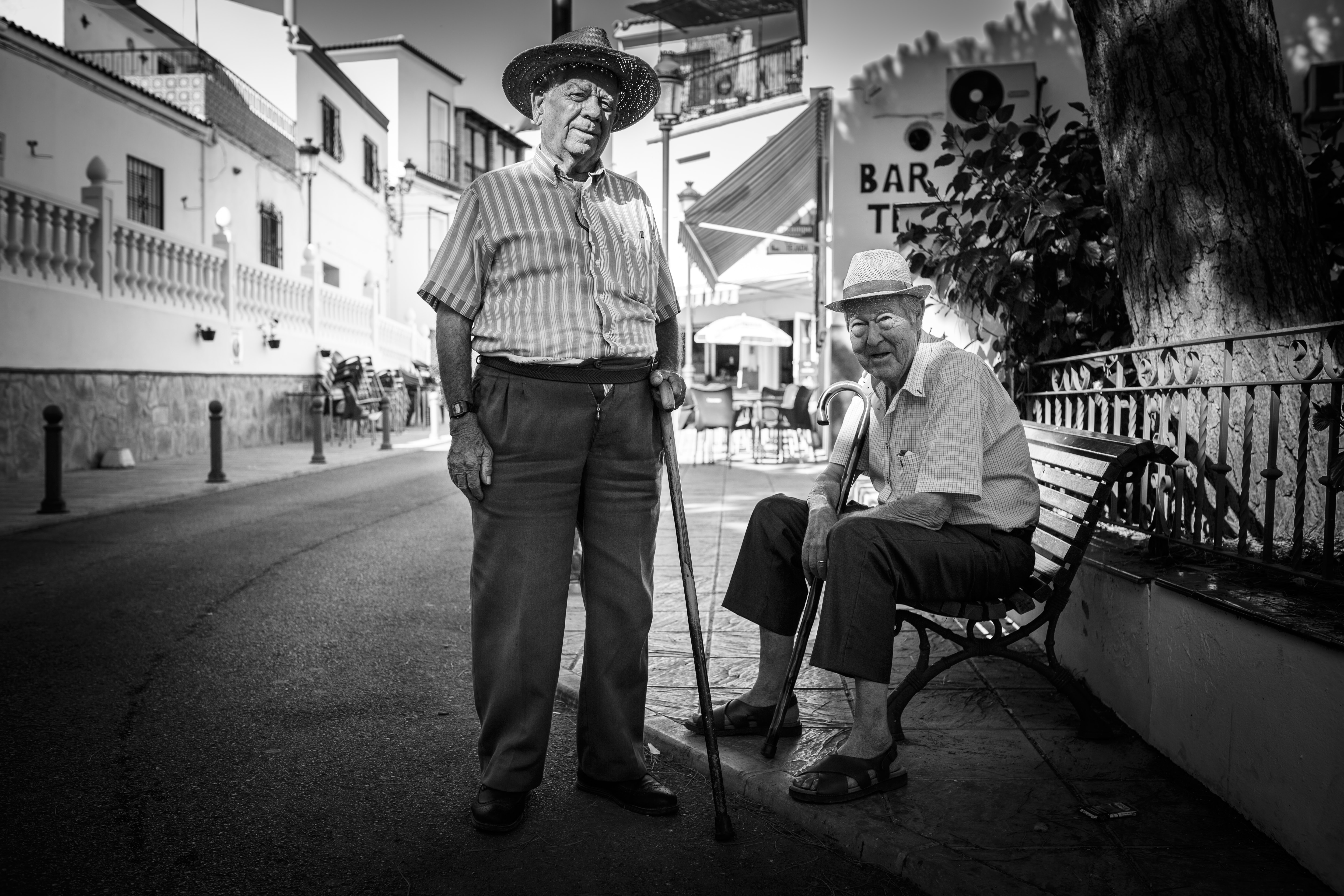 Black and white photograph of two older males, sitting on a bench and standing with a cane.