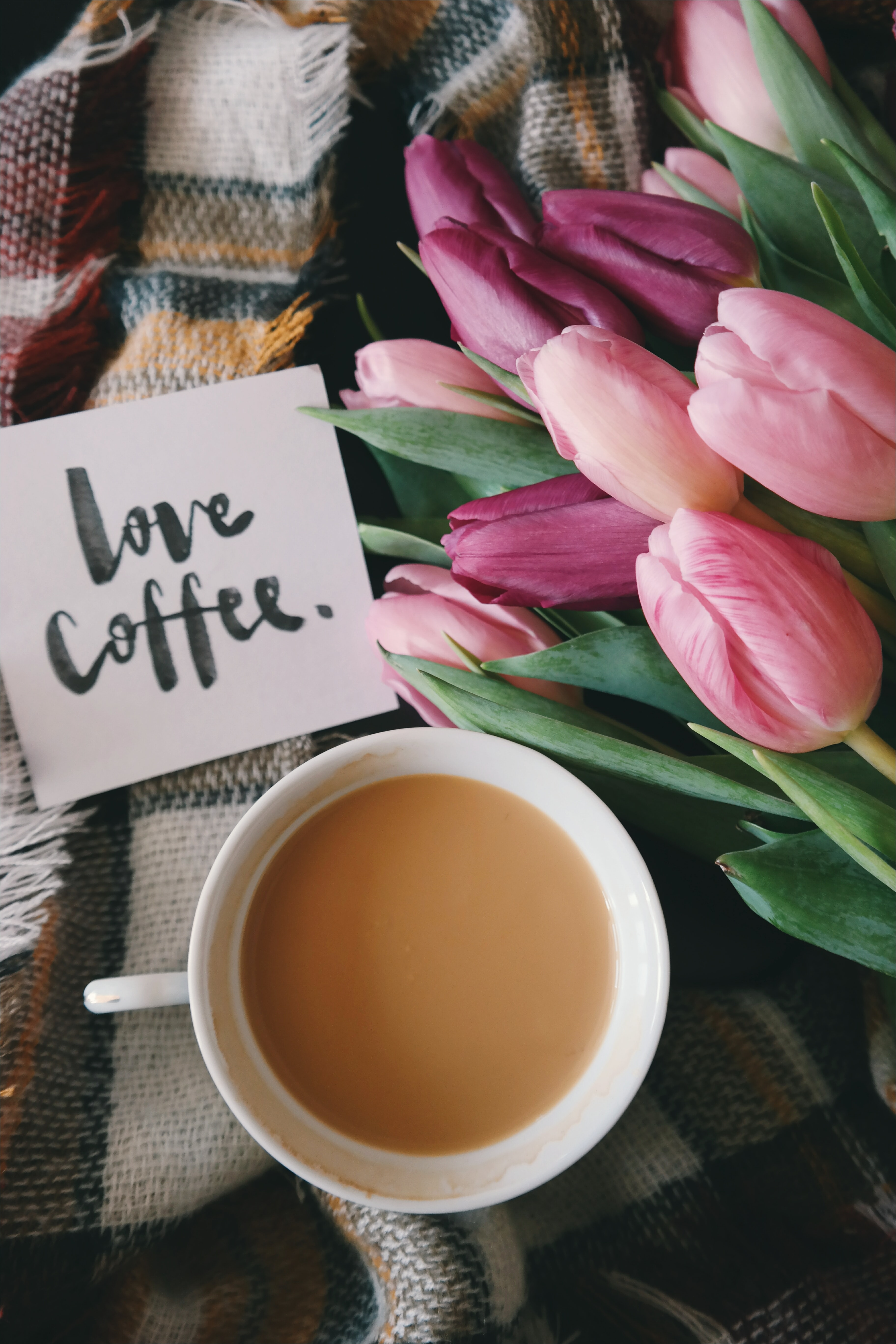 "A ""love coffee,"" note next to a creamy cup of coffee and flowers."