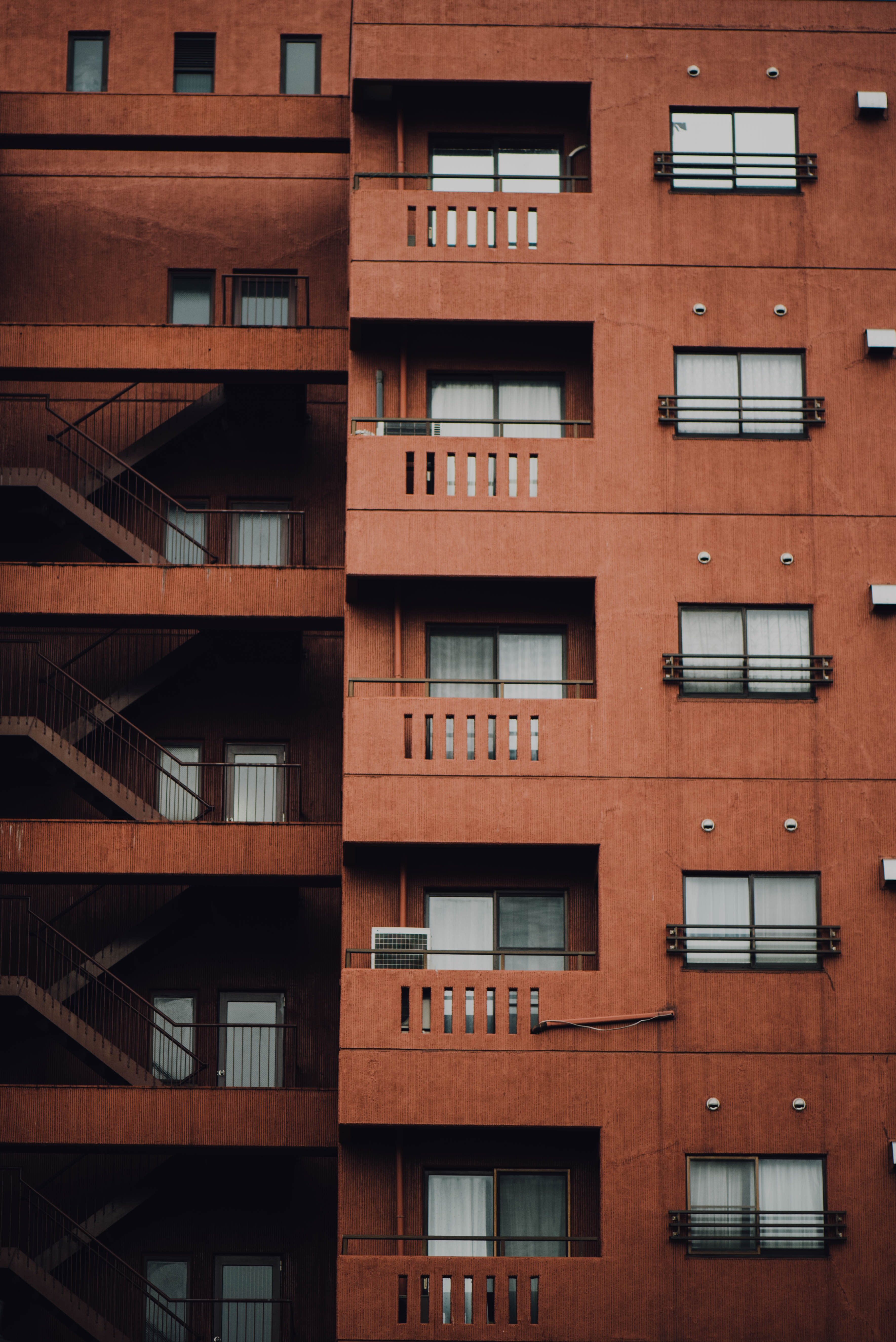 Facade of a brown apartment building consists of the stairwells, balconies, and windows.