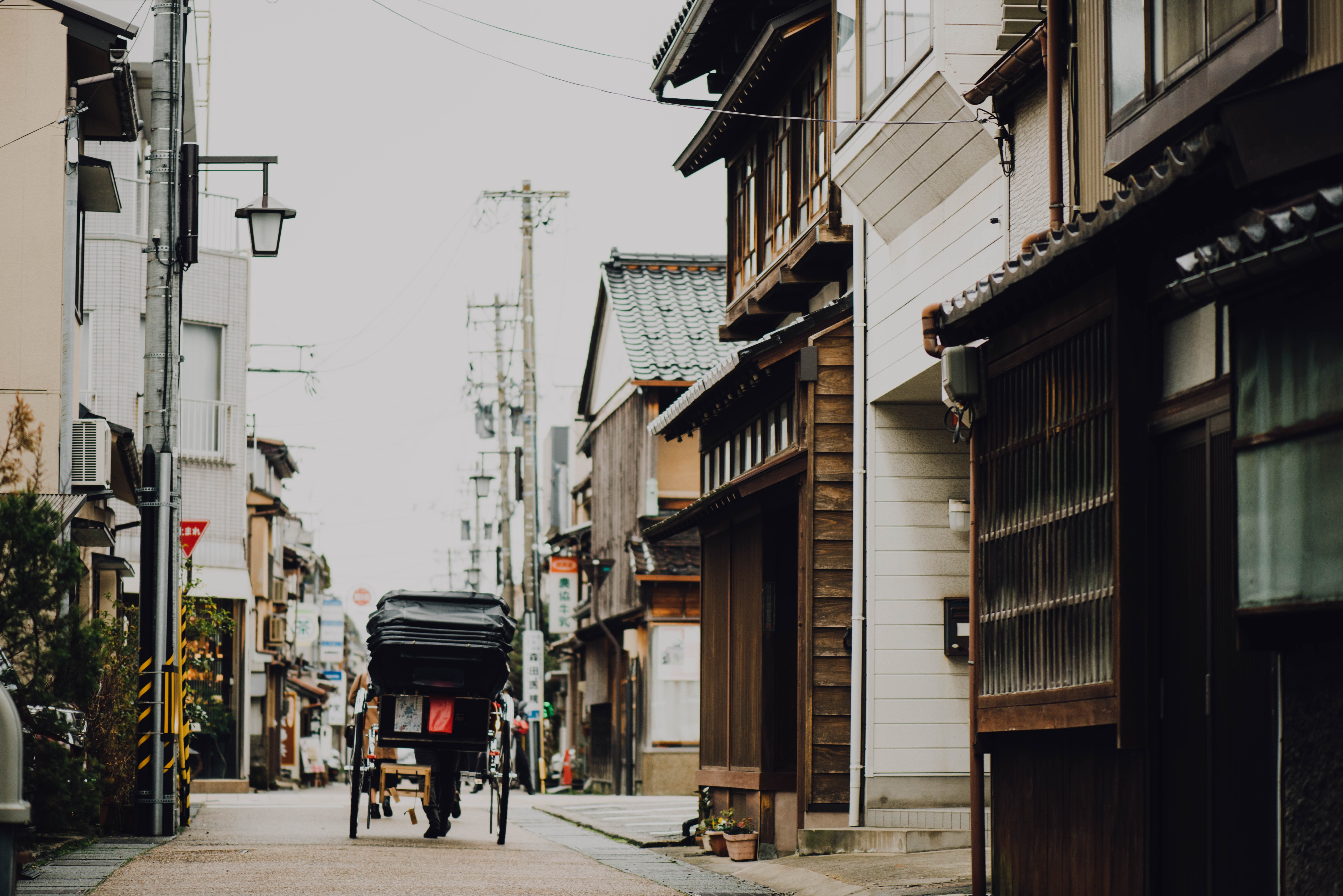 Asian street with a carriage going down the road lined with buildings and power lines