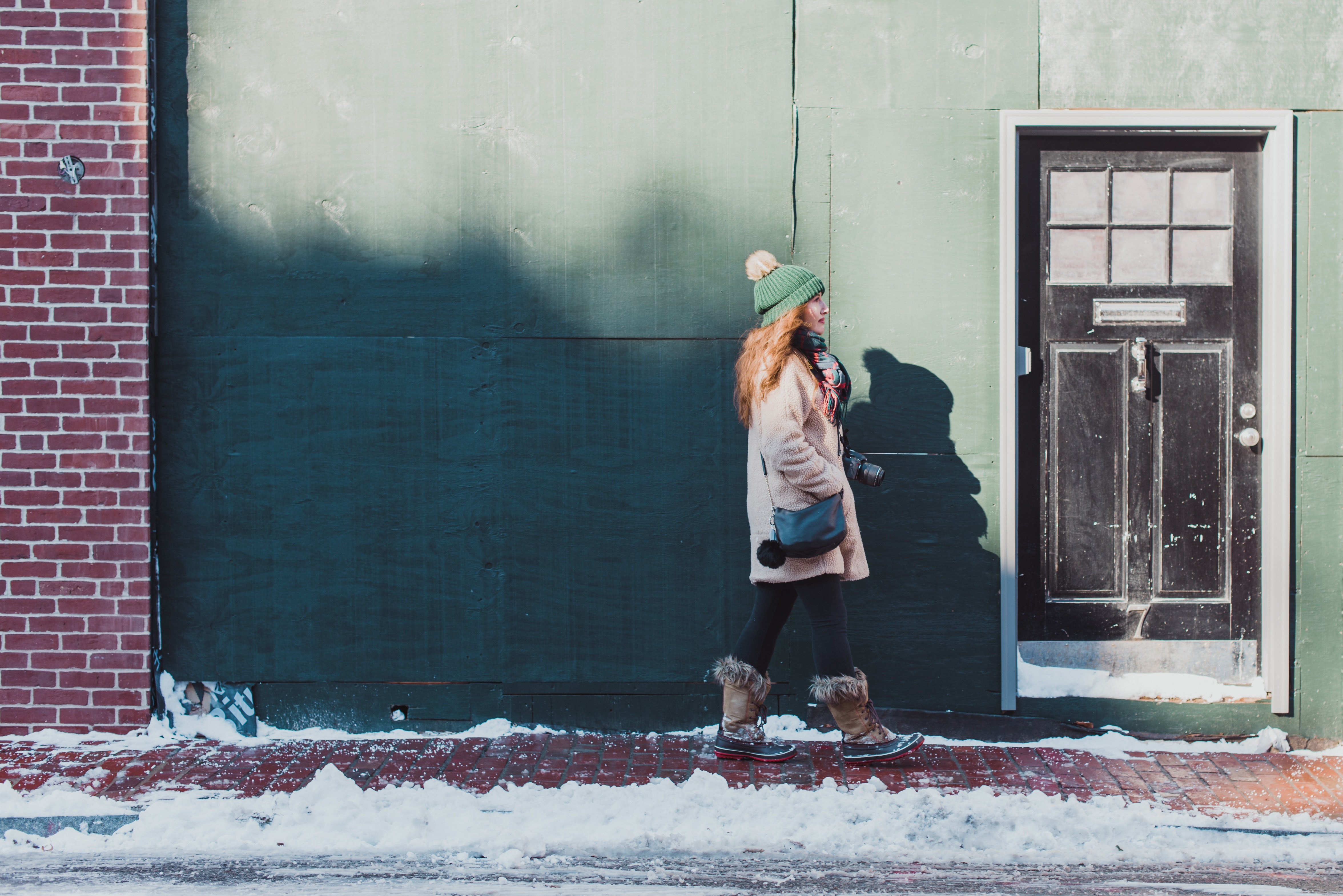 woman standing beside wall and door during daytime