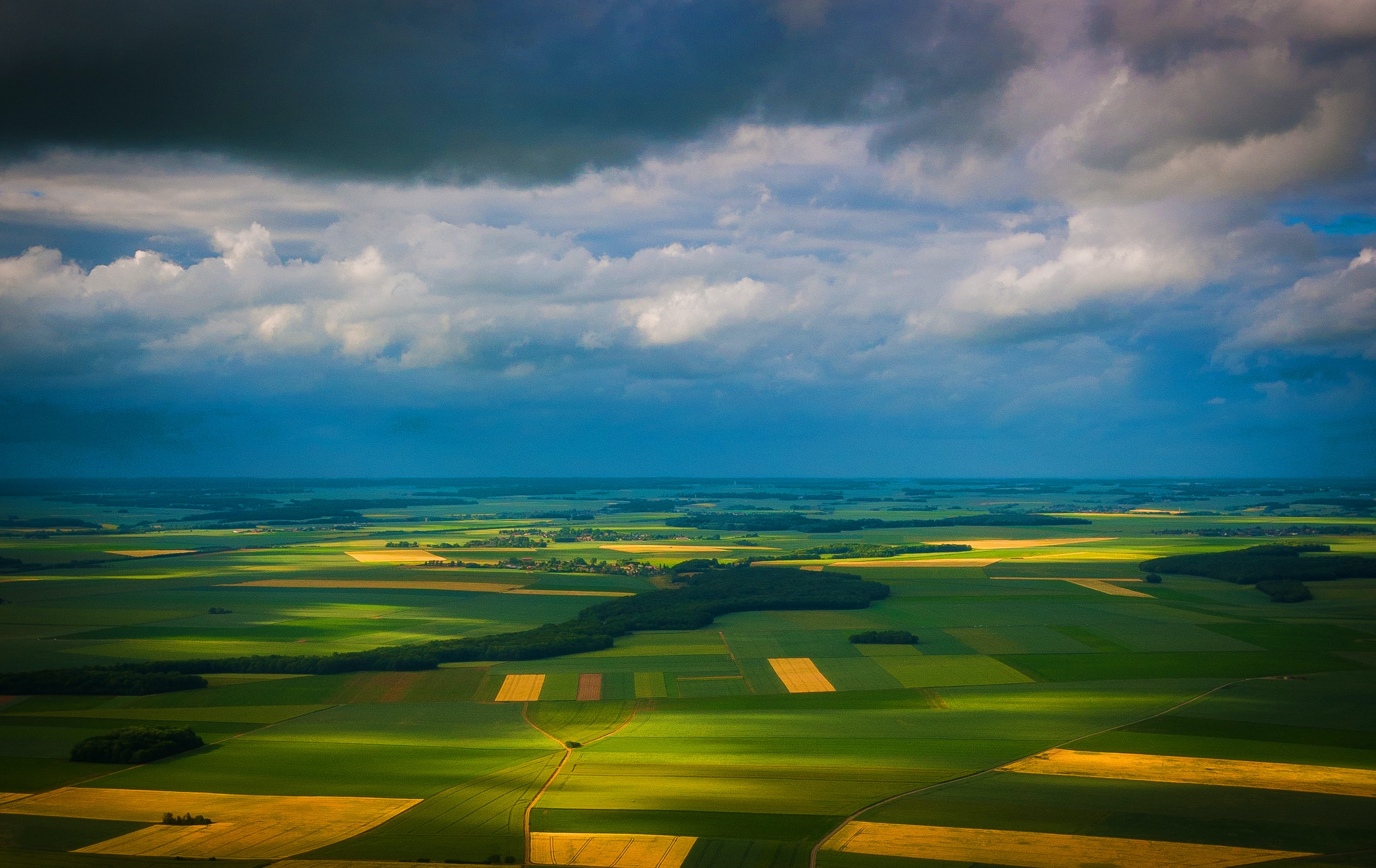 Wide shot of green and yellow agricultural fields with clouds overhead