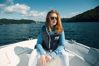 woman sitting on boat near mountain during daytime
