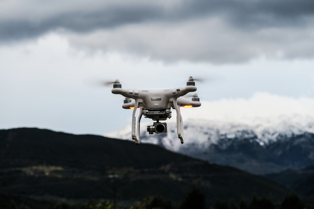 flying white quadcopter drone at daytime