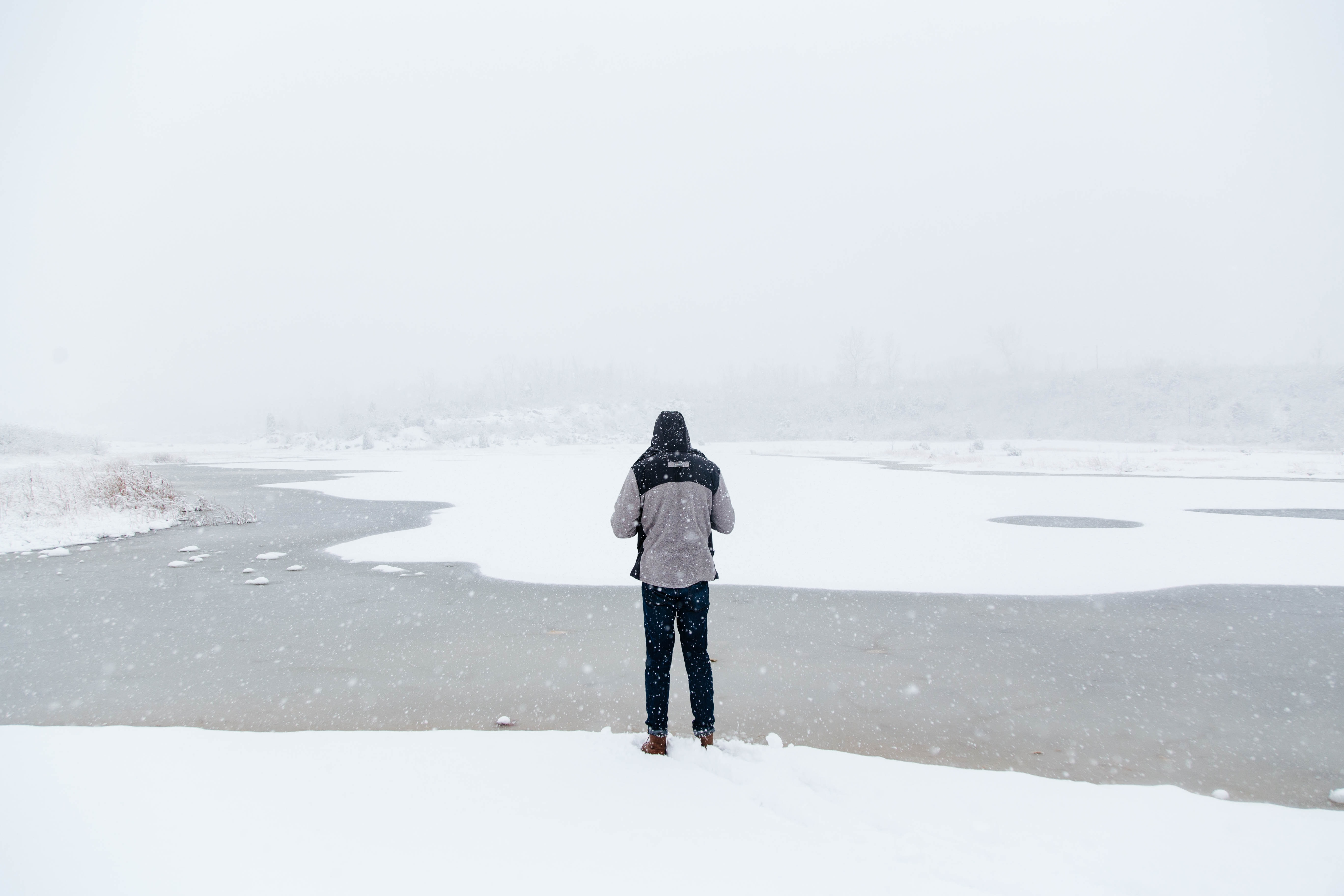 A man standing at the water looking into the fog in Oakes Quarry Park in Ohio