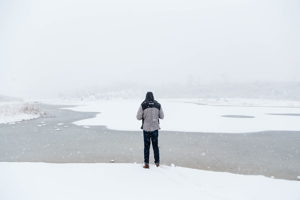 man standing on snow field facing river