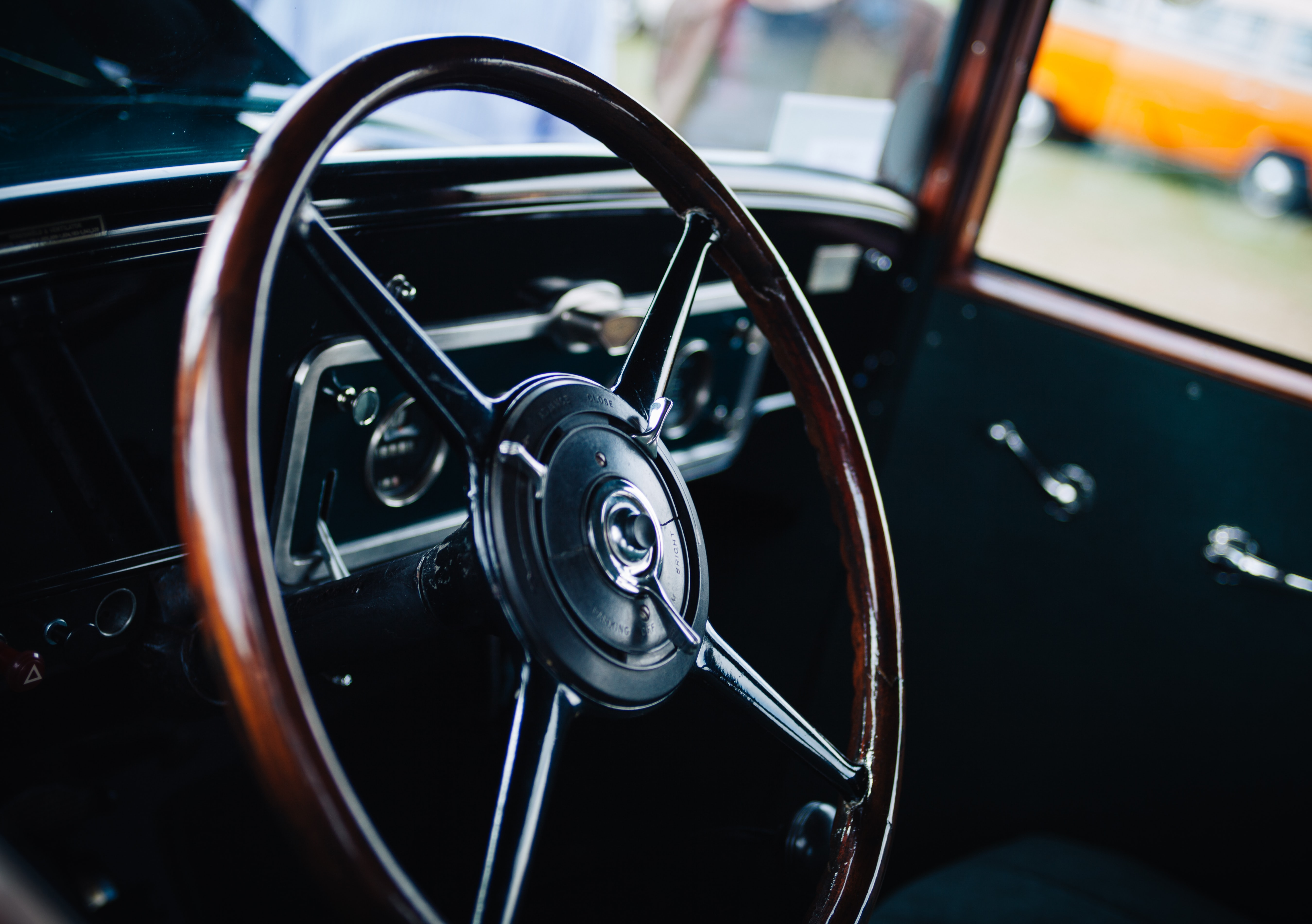 Old vintage car interior with the wooden frame steering wheel