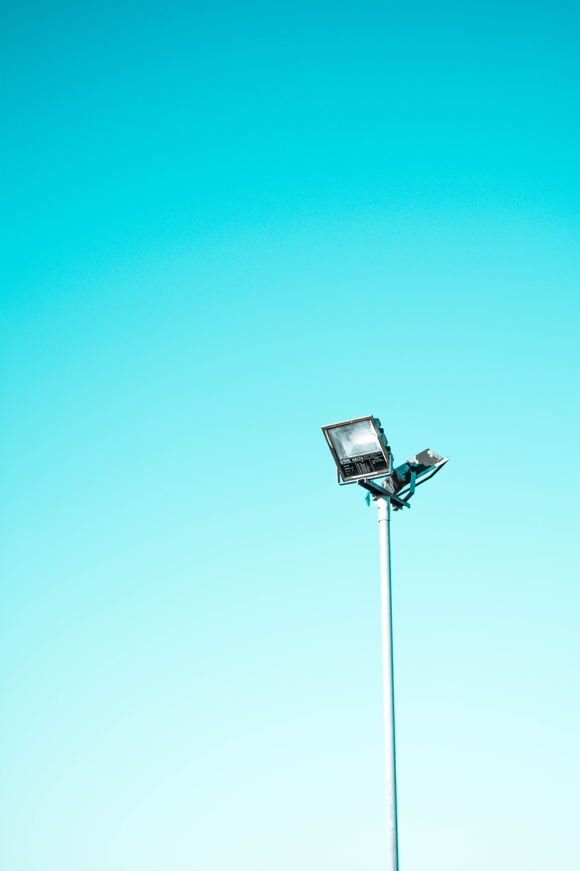 white and black light post under blue sky