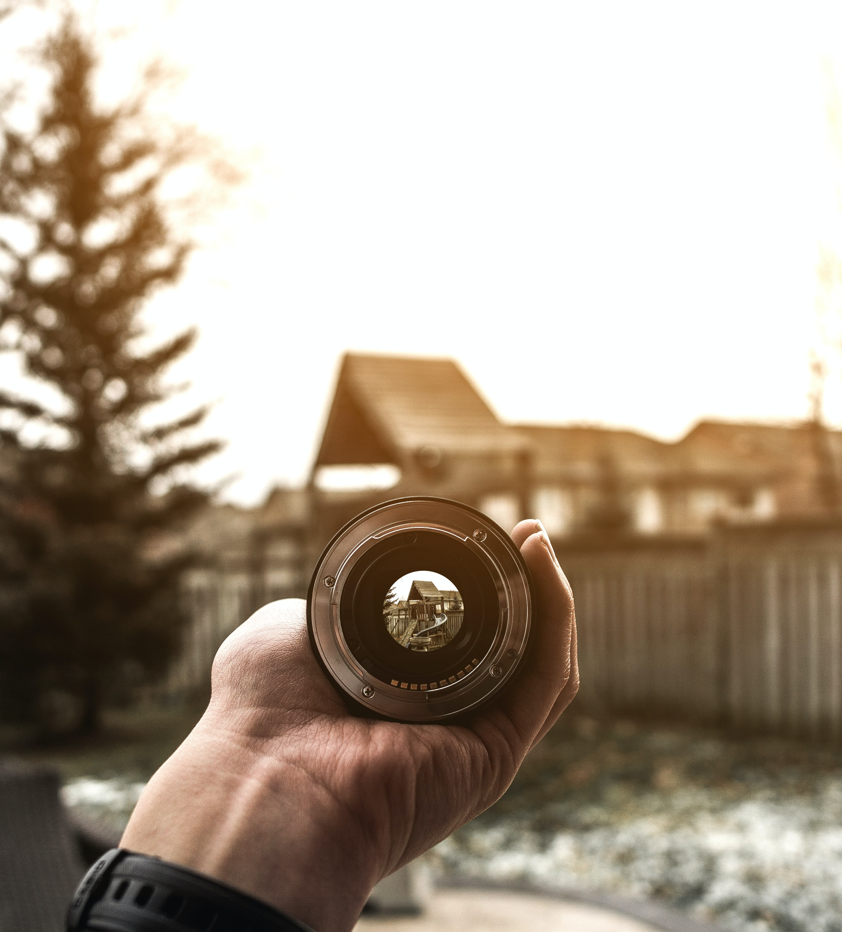 Close-up of a hand holding a camera lens pointed at a small hut