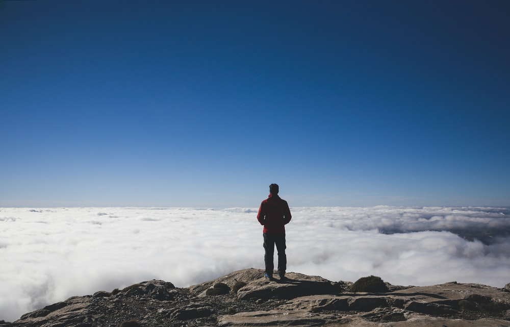 man standing on brown mountains facing sea of clouds