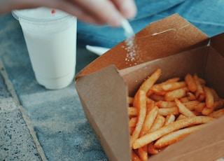 person sprinkling salt in fries
