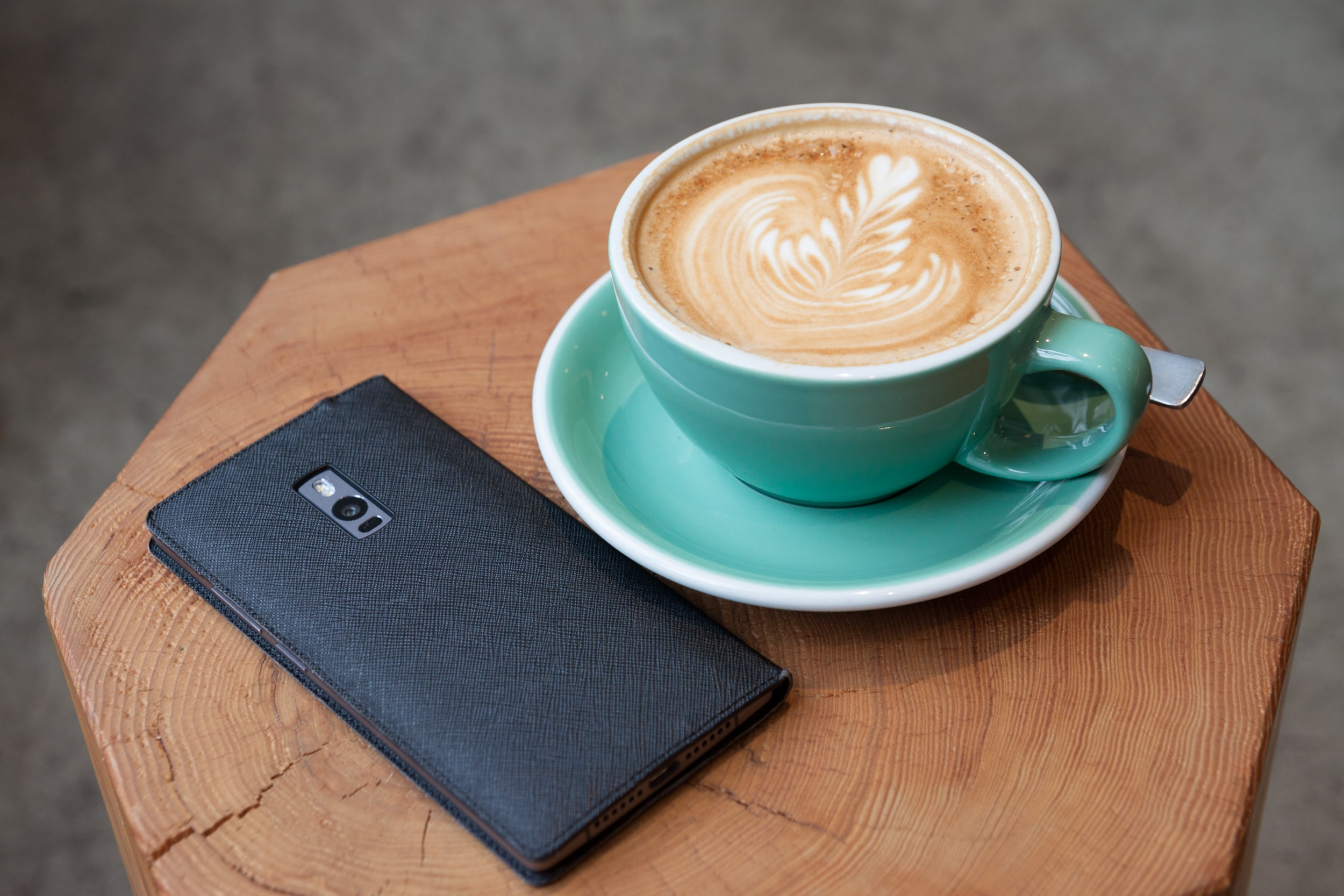 A smartphone on a wooden surface next to a cup of coffee with latte art