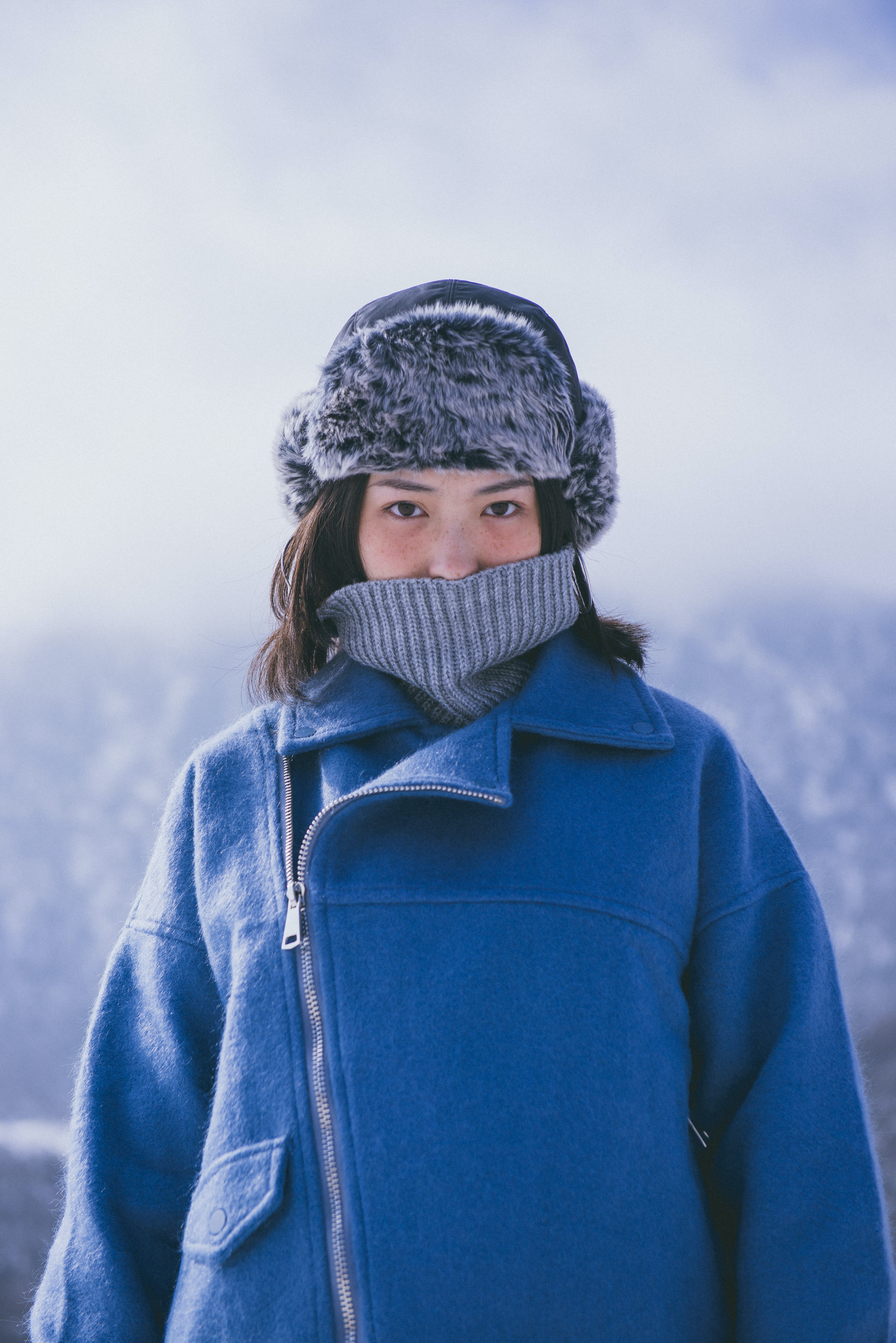Woman bundled up in all blue winter coat and hat