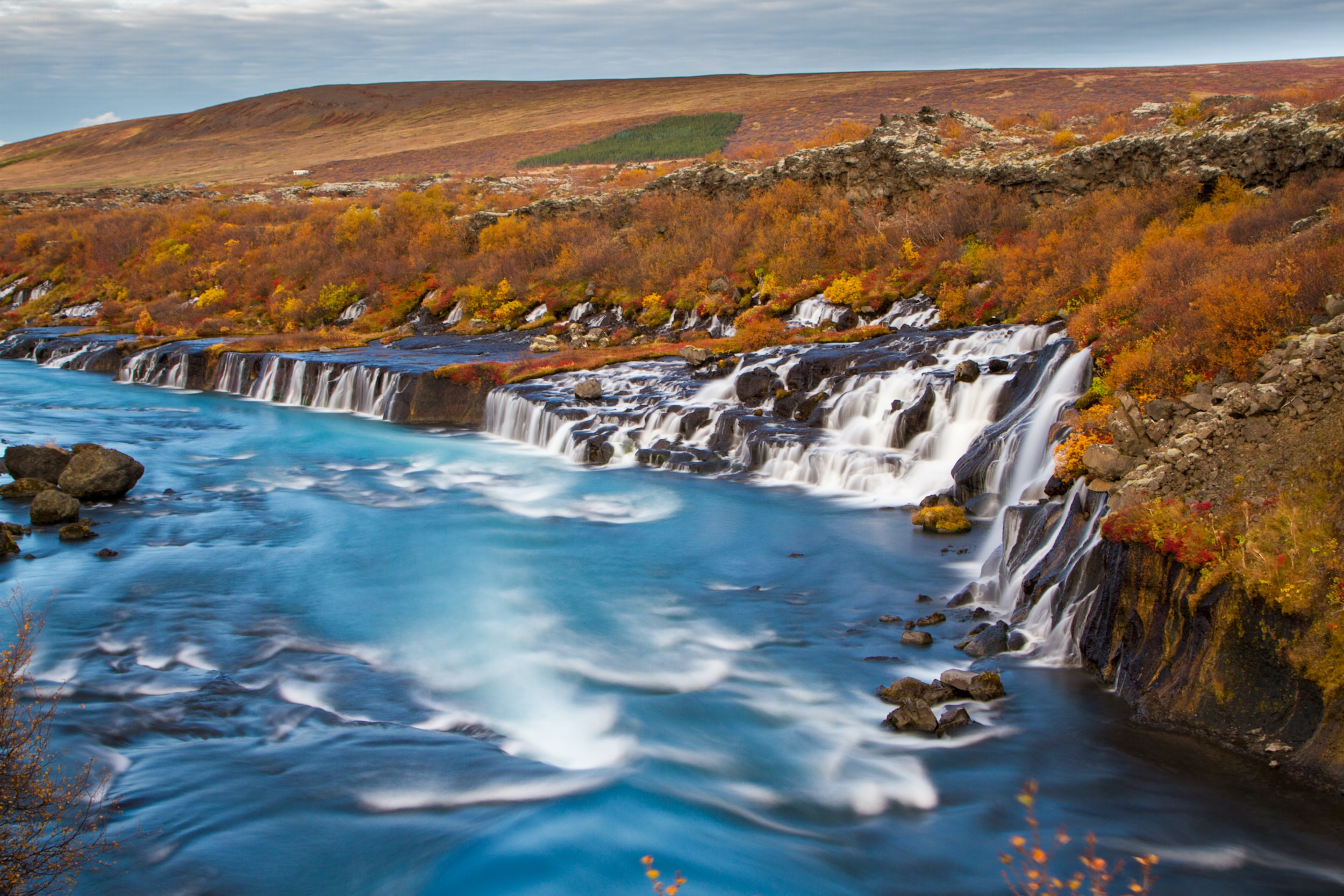 HDR photo of whitewater waterfalls from a hilly rocky edge beside a forest of autumn trees cascading down a clear and fast moving river