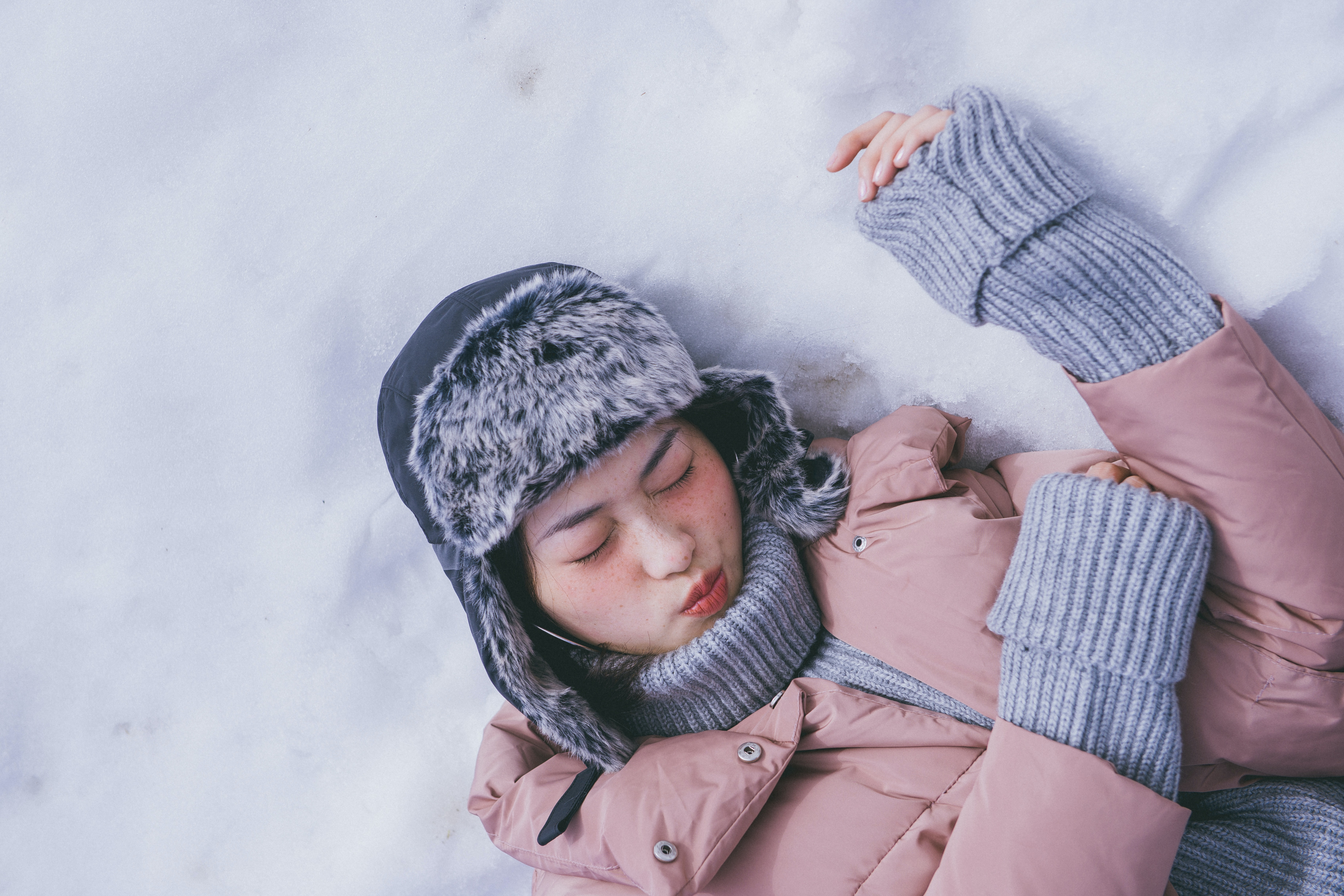 Uncomfortable woman making a pained expression laying in the snow
