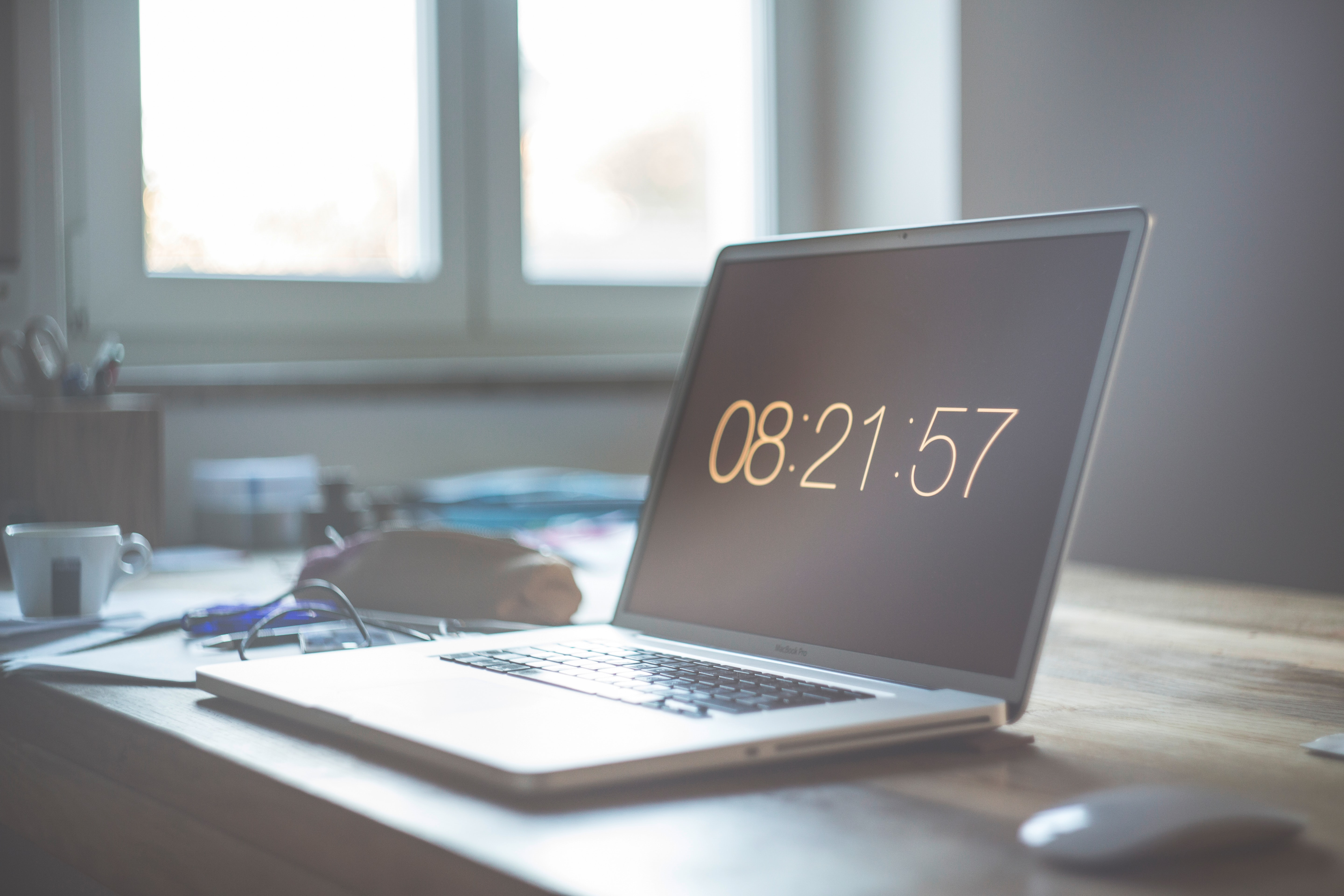The time displayed on the dimmed screen of a MacBook on a messy desk