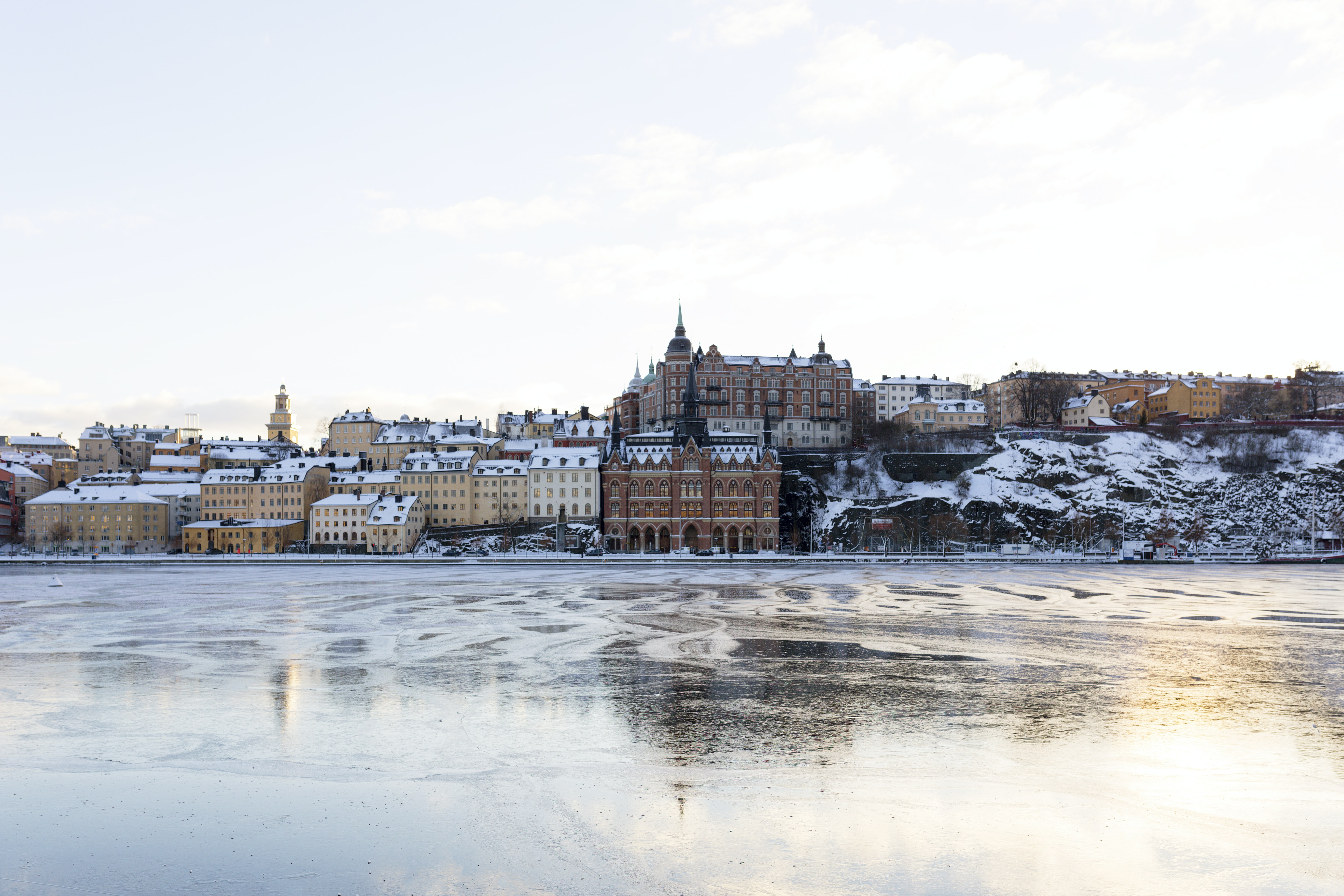 A Swedish city with tan and brown buildings by the shore of a frozen lake
