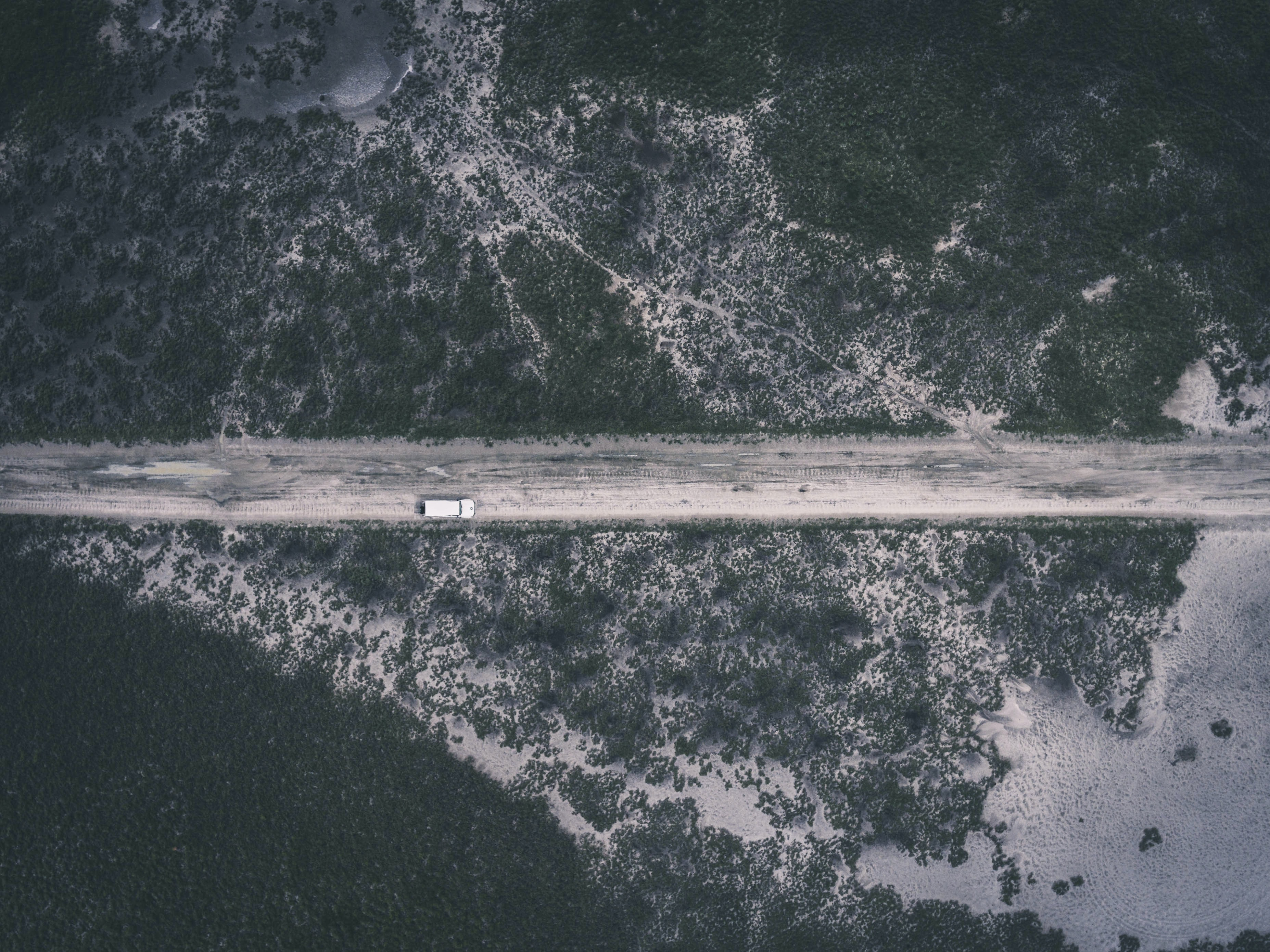 A drone shot of a white car on a dirt road through the wilderness