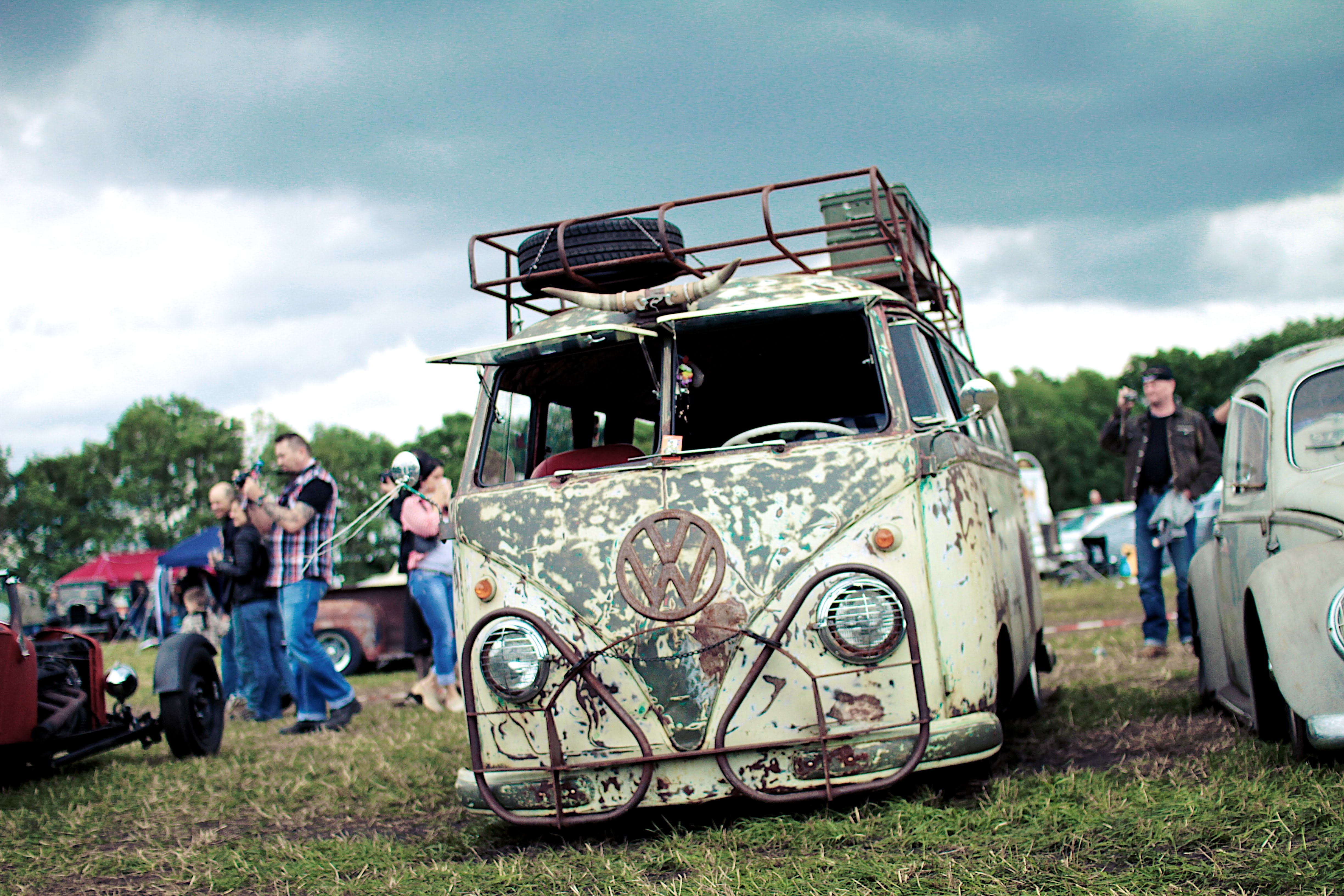 People view rusted vintage Volkswagon bus at a car show.