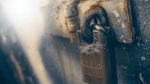 brown padlock in black wooden door