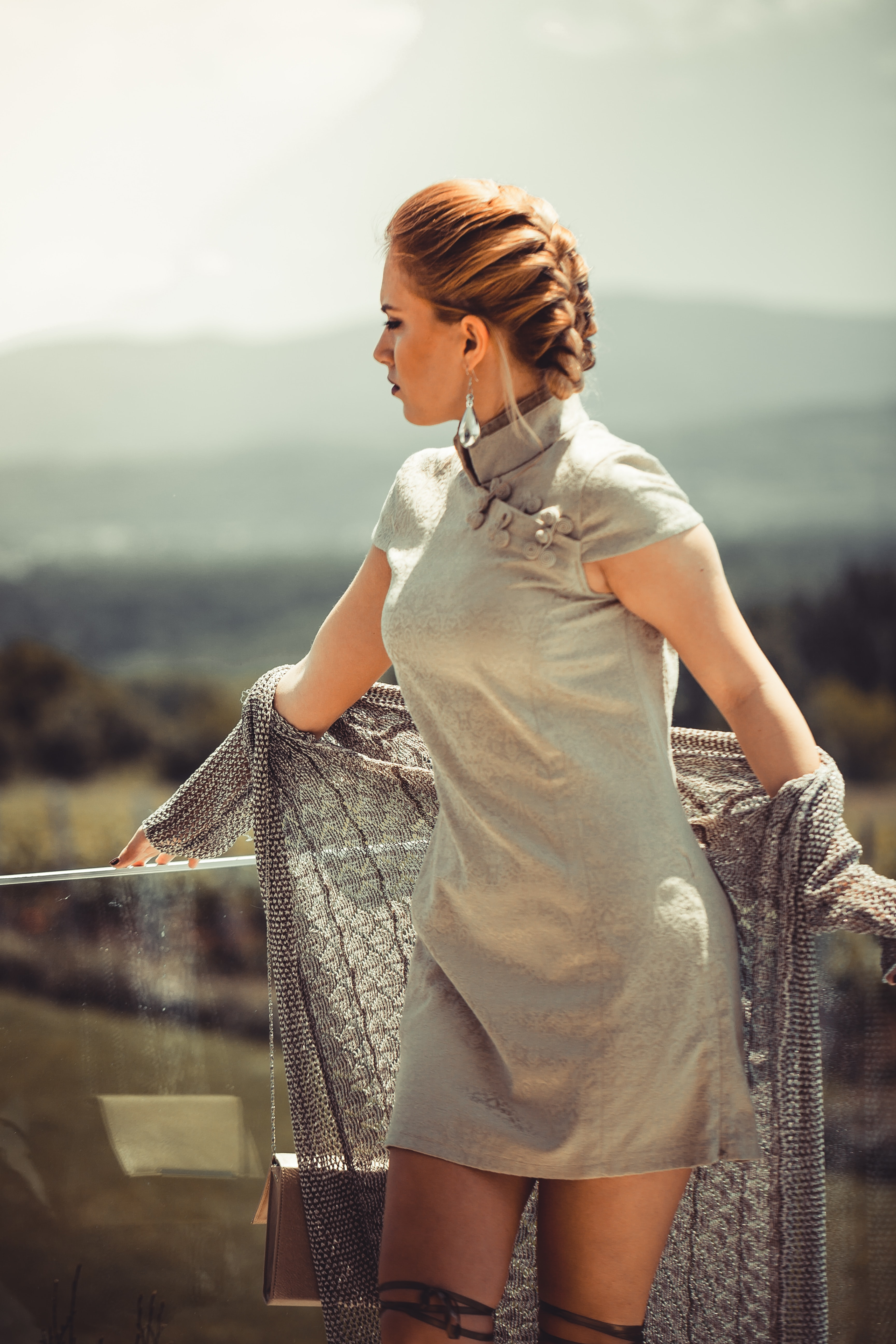 braided hair woman taking photo in corner of glass railings at daytime