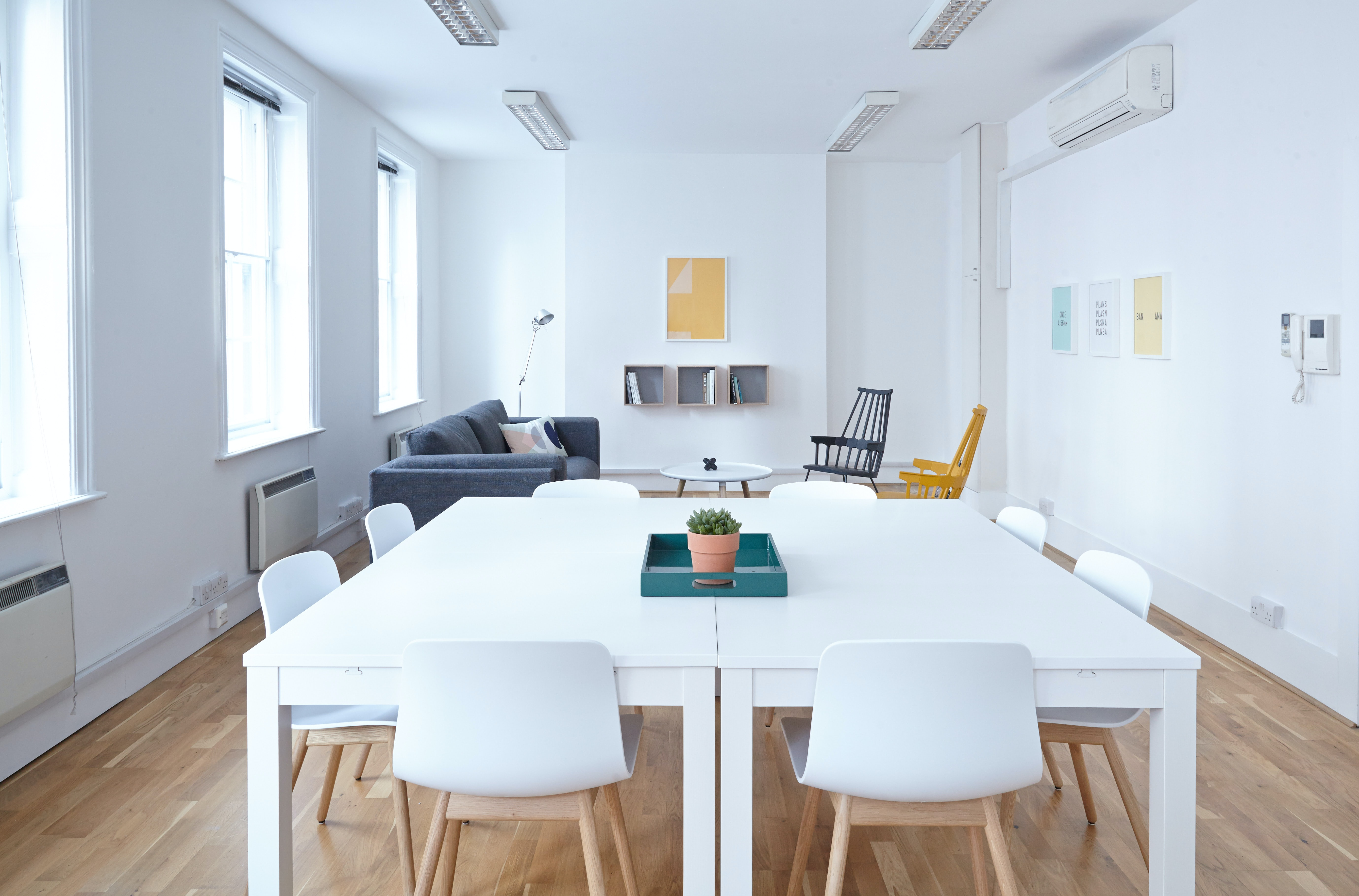 Two white tables joined together in a clean white room with a sofa