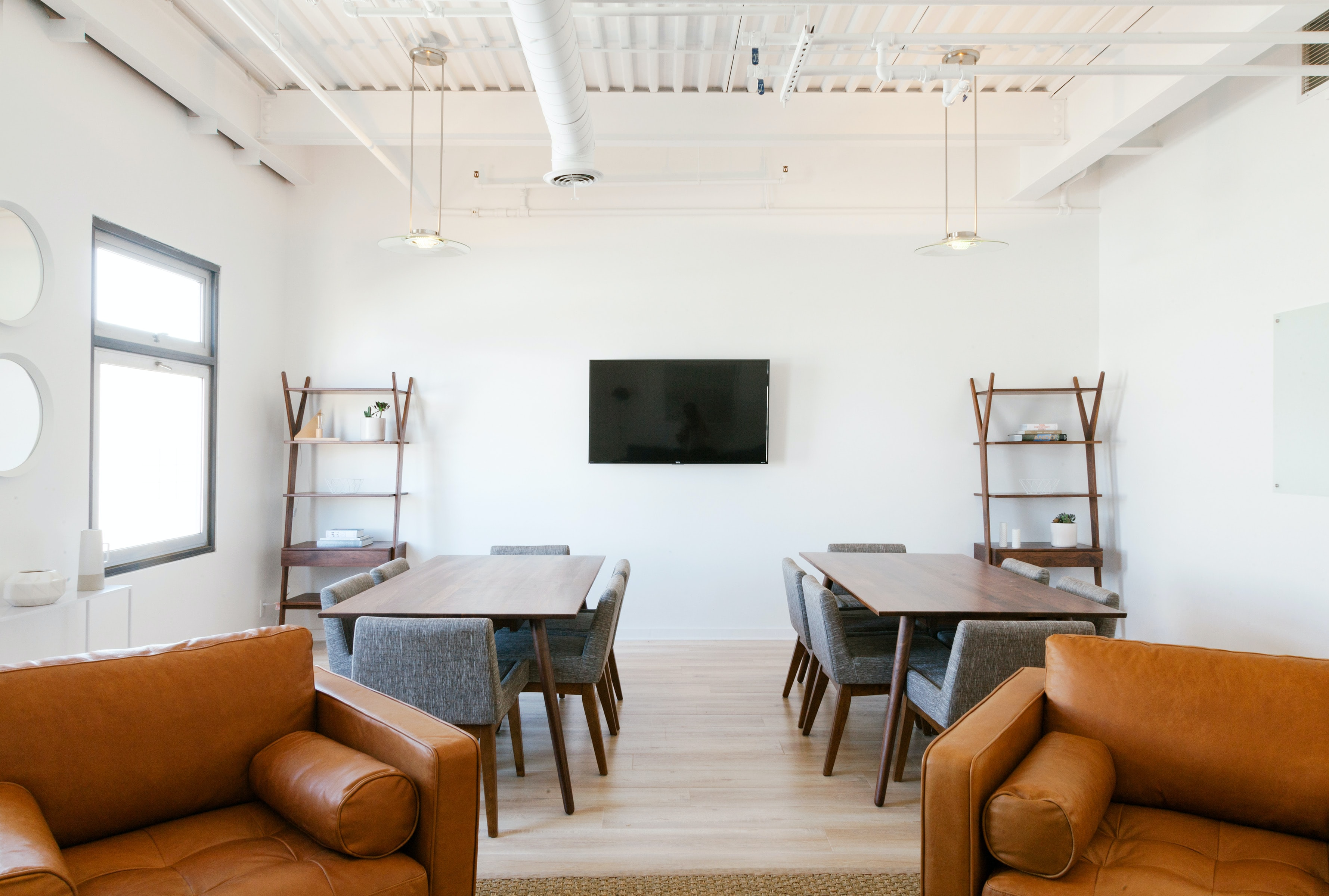 Two leather armchairs and two tables in a meeting room with a television