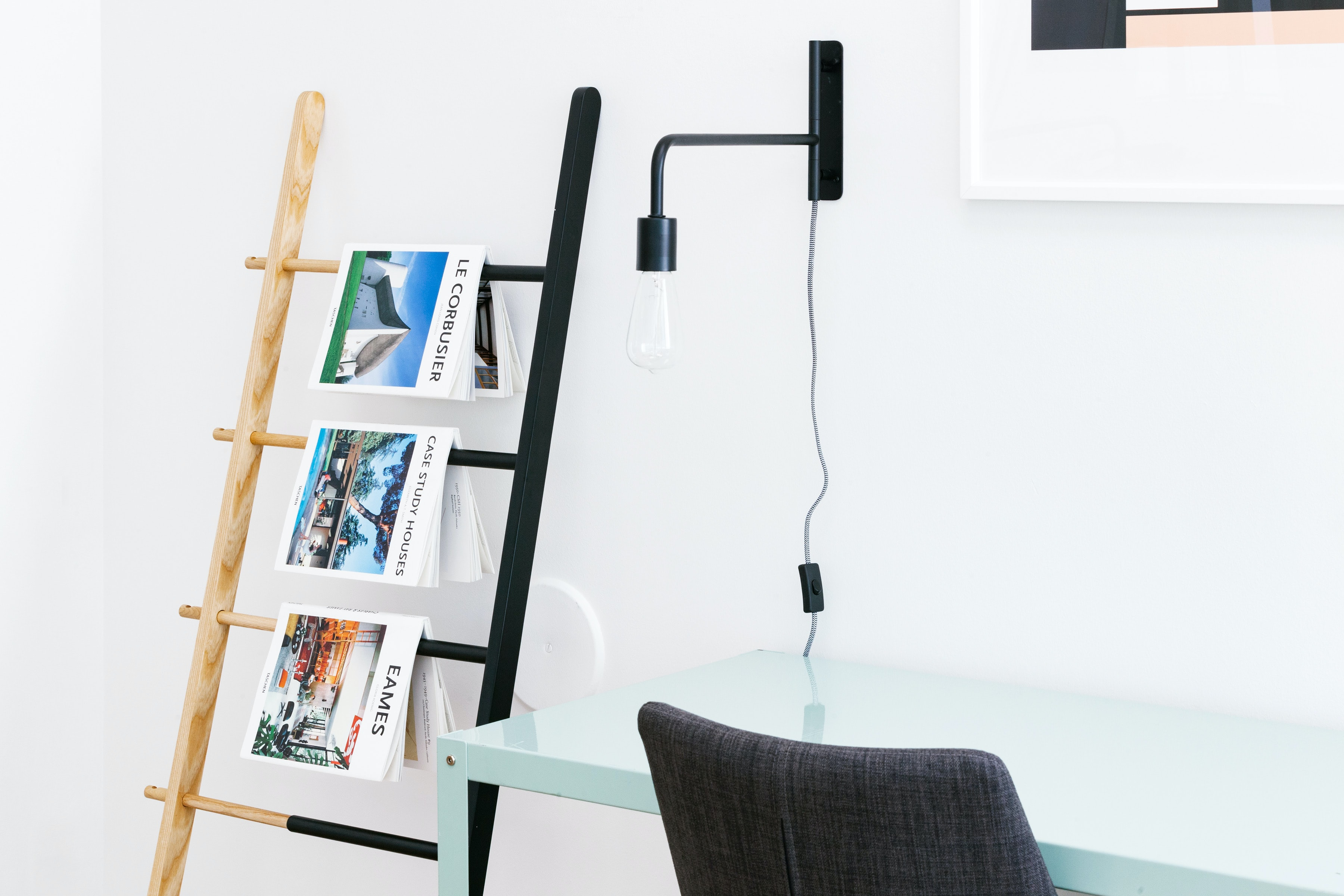 Magazines on architecture hanging from a ladder in a minimal interior