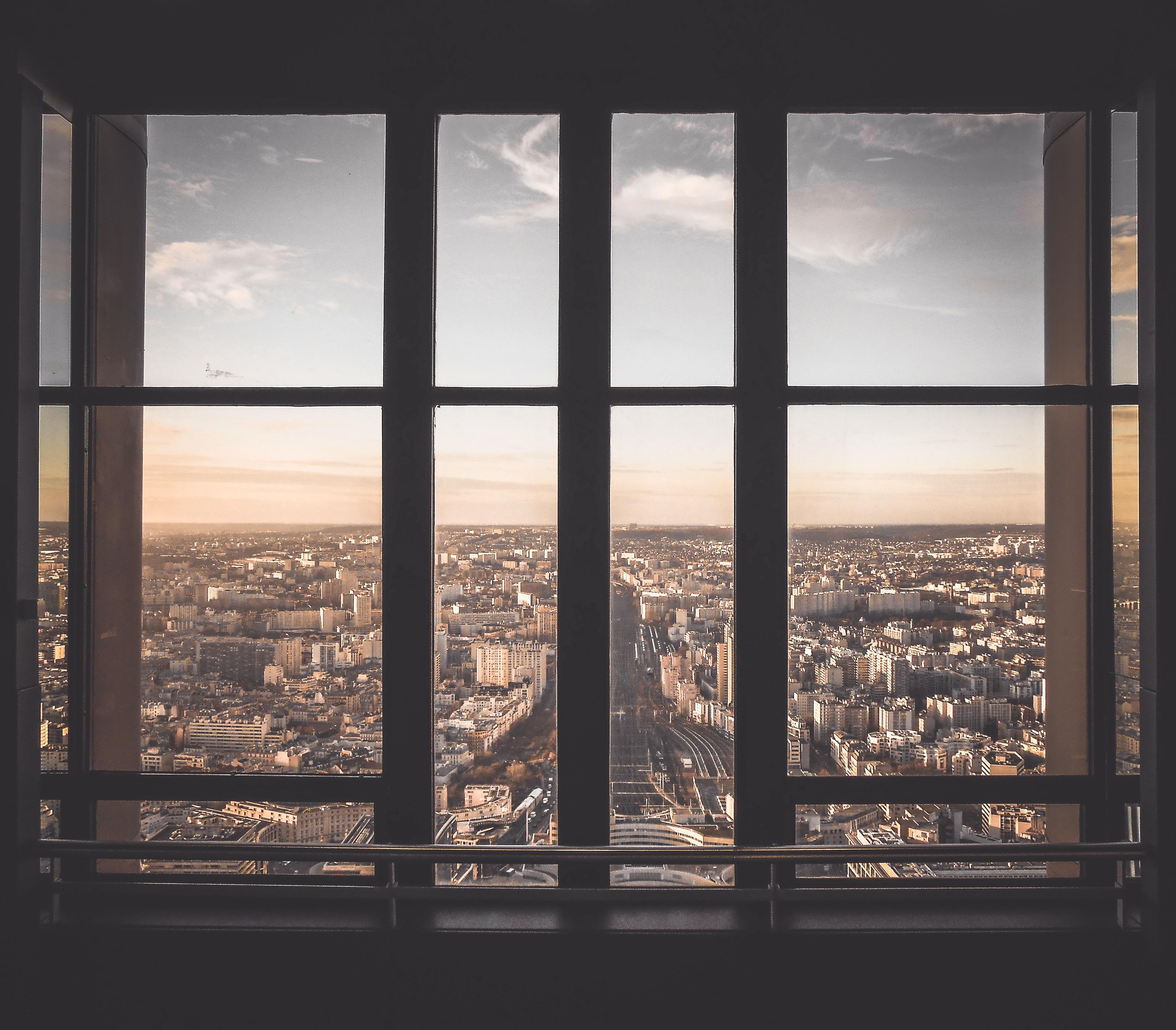 glass panel window showing city buildings under blue sky