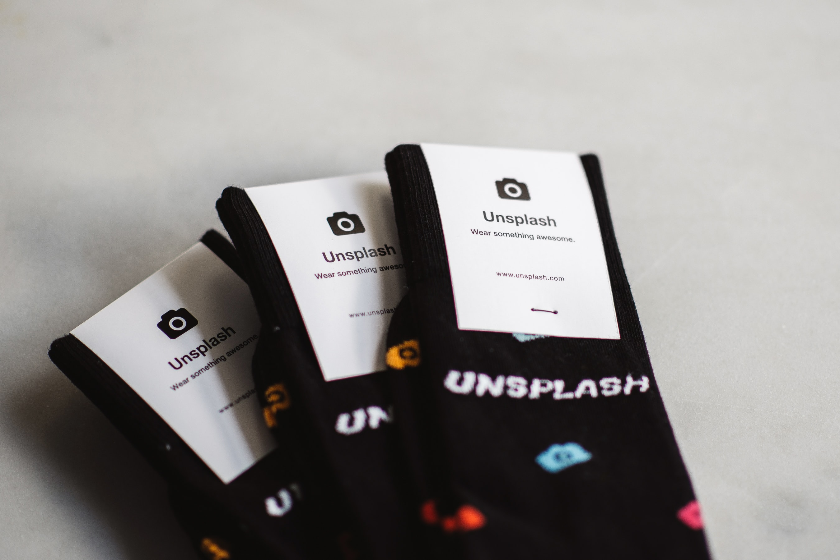 Three pairs of black socks with multicolor camera icons on them with white Unsplash labels