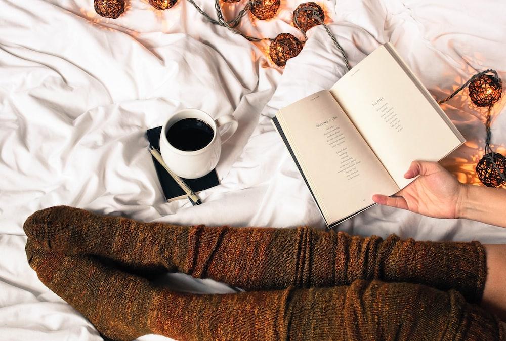mug of black coffee beside person's feet wearing brown stockigns