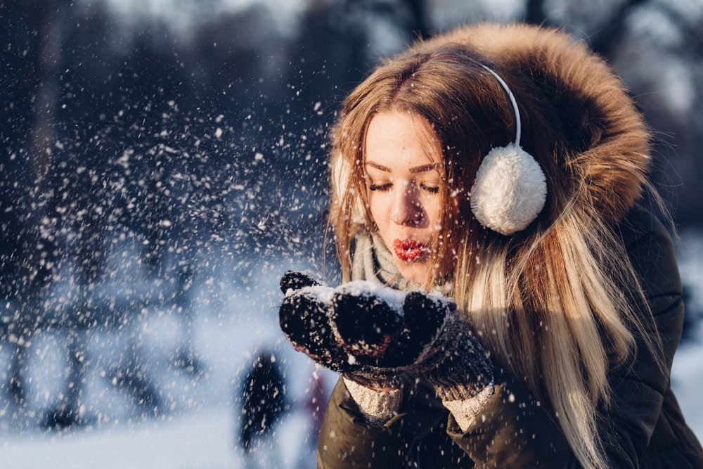 woman blowing snow on her hands