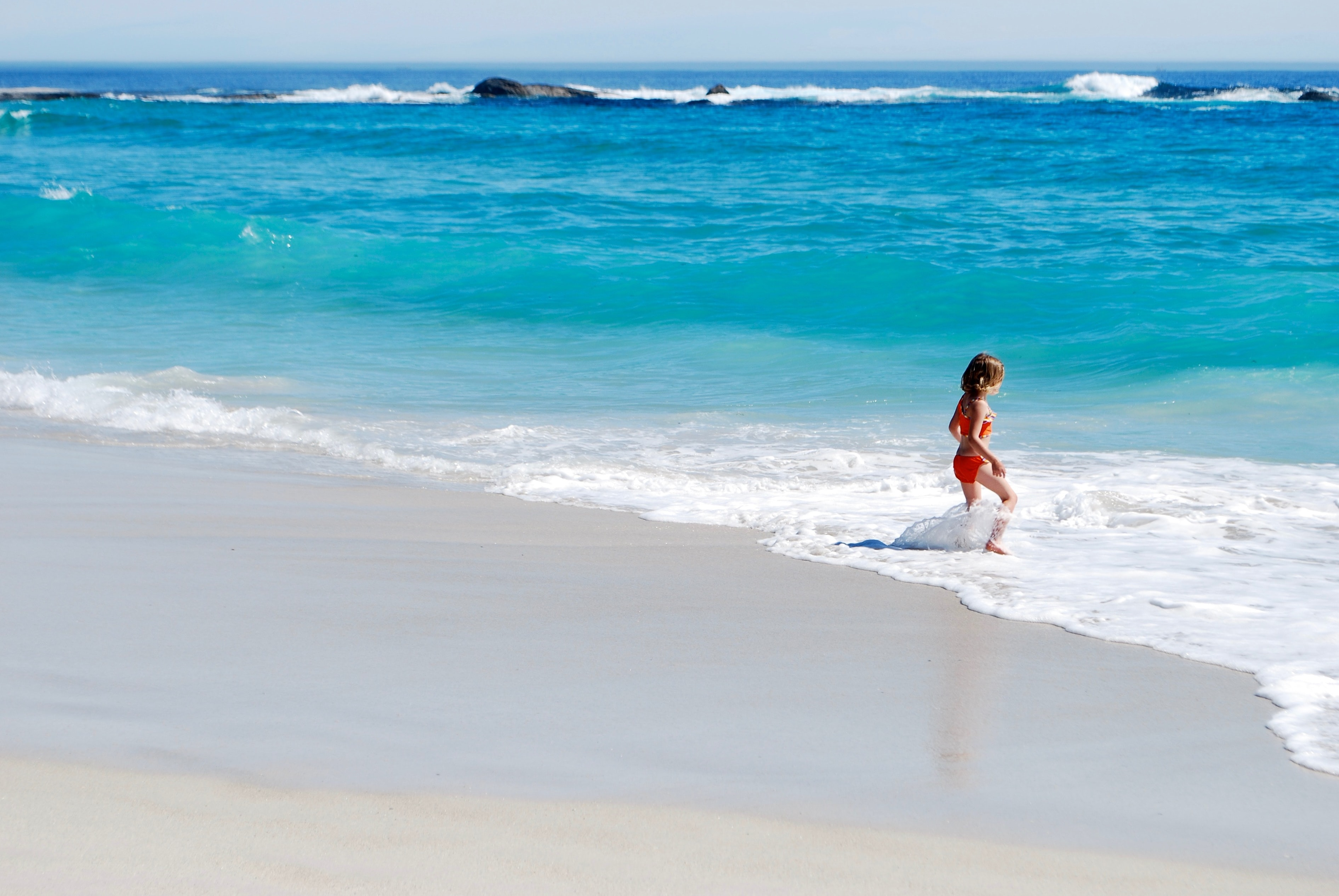 A small girl playing in the small waves on the seashore
