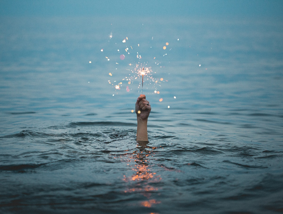 A body of water with a hand holding a sparkler